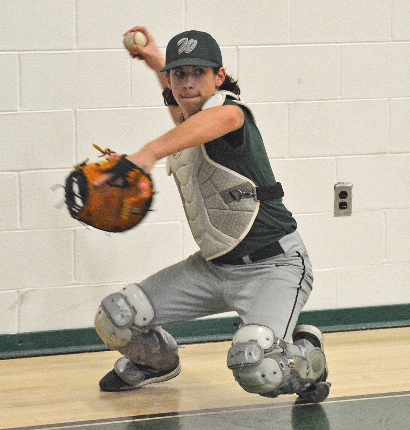 WORKING BEHIND THE PLATE — Westmoreland catcher Caleb Miller practices in the gym of Westmoreland High School during a recent workout. The freshman is one of five returning players for the Bulldogs.