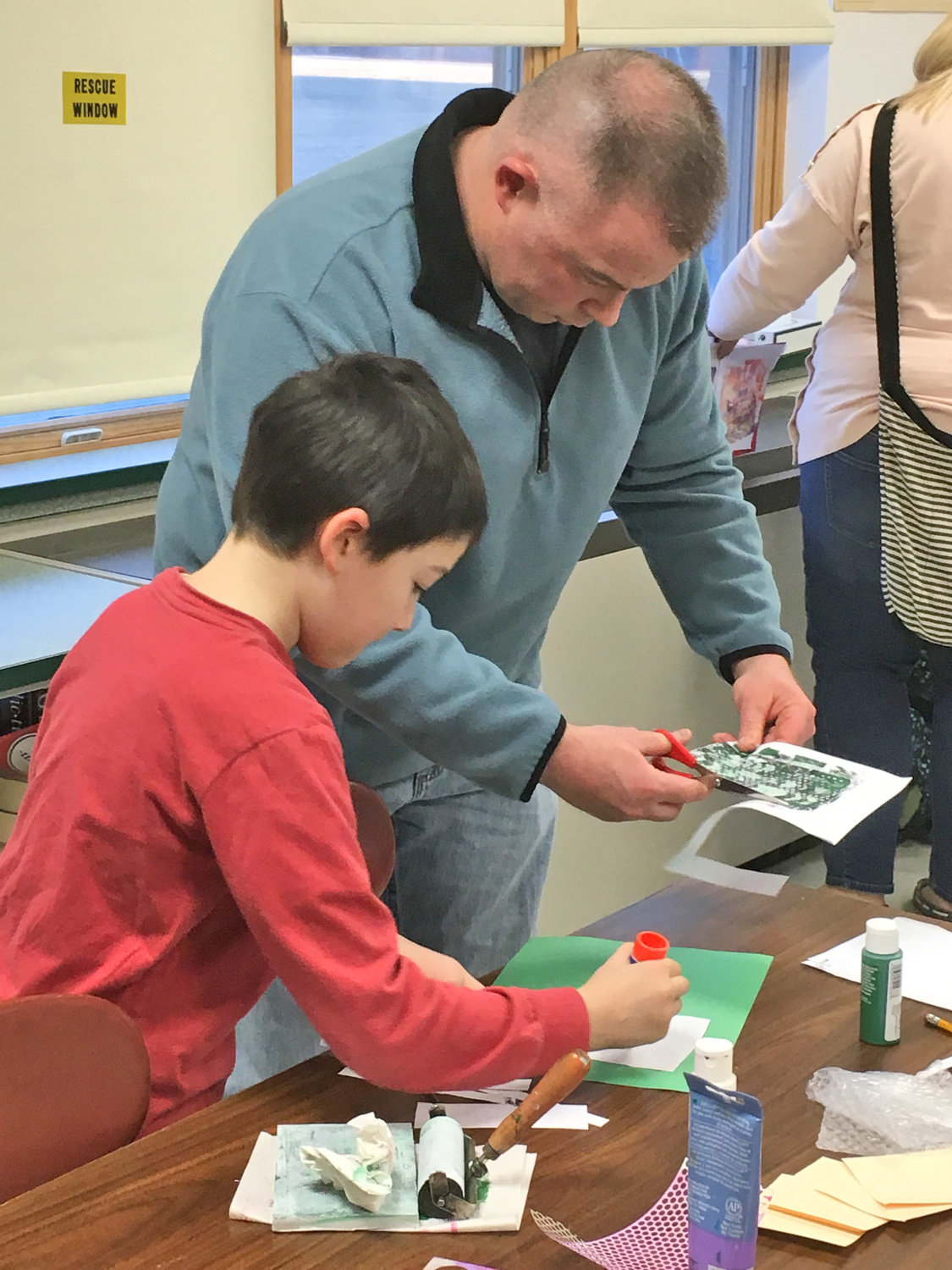 UNIQUE ART — Jim Hayes and son Keegan, third grade, make one-of-a-kind mono prints during a special activity that was part of the ZI3 Adventure Night at Westmoreland Upper Elementary School.
