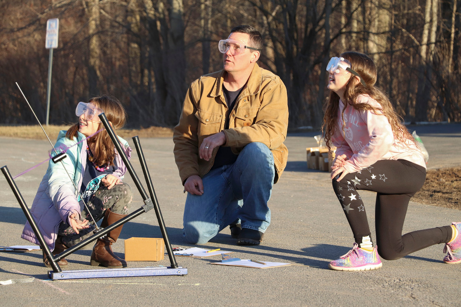 UP AND AWAY — A dad and two girls watch as their rocket takes off during the ZI3 STEAM Adventure Night at Westmoreland Upper Elementary School March 27.