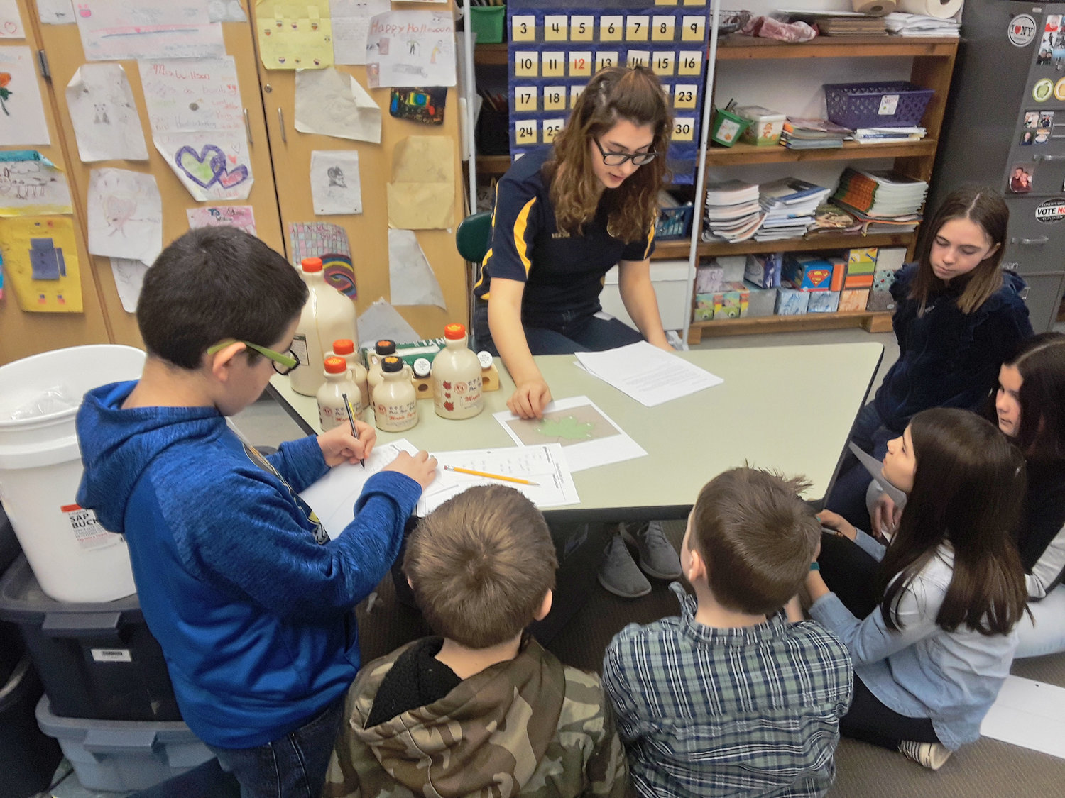 LESSON ON MAPLE TOPICS — Camden Middle School students learn about maple leaf identification from Vernon-Verona-Sherrill FFA student Molly Adams, at center.