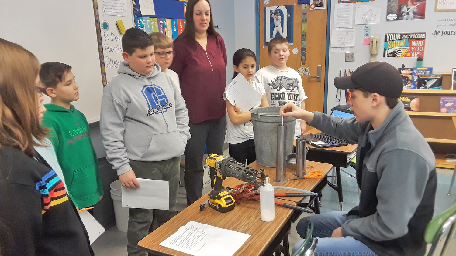 MAPLE PRODUCTION STEPS — Vernon-Verona-Sherrill FFA student Peter Makarchuk, at right, explains a hydrometer to Camden Middle School students, as part of a presentation on how maple syrup is made.