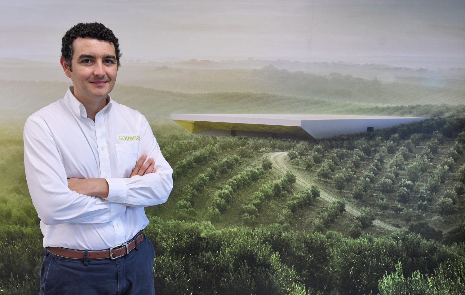 ROOTS OF SUCCESS — Sovena USA Inc. Managing Director Jorge Pena stands in front of an image at the company's Griffiss business park facility that shows an olive oil farm and state-of-the-art olive oil mill in Portugal that is owned by the parent Sovena Group in this file photo. Sovena received the gold medal in the Light Green Fruity category in the Mario Solinas Quality Award competition, organized by the International Olive Council and considered the most prestigious olive oil contest in the world, according to the company.