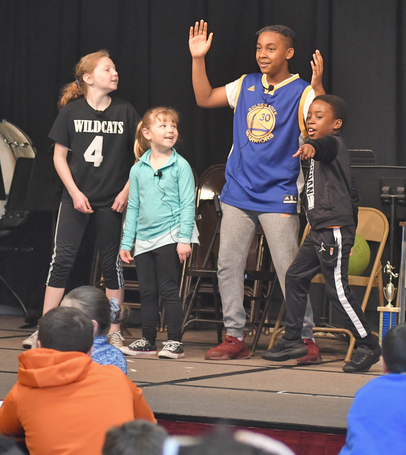 "STUDENT PLAYWRIGHTS AND PERFORMERS — A play called ""One v. One,"" written by Ridge Mills Elementary School sixth-graders Isabella O'Rourke and Isiah DeJean, is performed by them with versions of their ""younger selves,"" played by first-graders Livia O'Rourke and Boluwarin Adeyeye, on Thursday at the school as they sing ""Stand by Me."" As part of a sixth-grade writing project whose theme involved paying it forward and acts of kindness, students produced literary works in genres such as historical fiction, realistic fiction, poetry and plays after reading the book ""Paying it Forward"" by Catherine Ryan Hyde. Among those implementing the project were sixth-grade teachers Sue Kaier and Kristin King along with resource teacher Tom Gates."