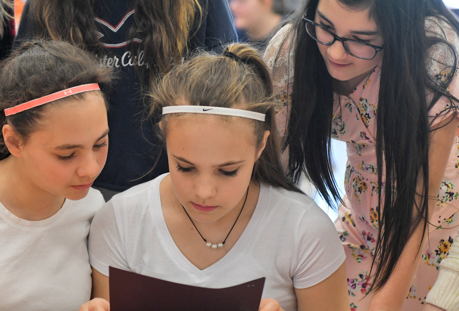 "GETTING THE WORDS — From left, Ridge Mills Elementary School sixth-graders Mariana Ciccone, Gracie Lucia and Lily Mirabelli look over a story during a reading session Thursday at the school, as part of a literacy event whose theme involved paying it forward and acts of kindness. A sixth-grade writing project included students reading the book ""Paying it Forward"" by Catherine Ryan Hyde and then producing literary works in genres such as historical fiction, realistic fiction, poetry and plays. Implementing the project were sixth-grade teachers Sue Kaier and Kristin King along with resource teacher Tom Gates."
