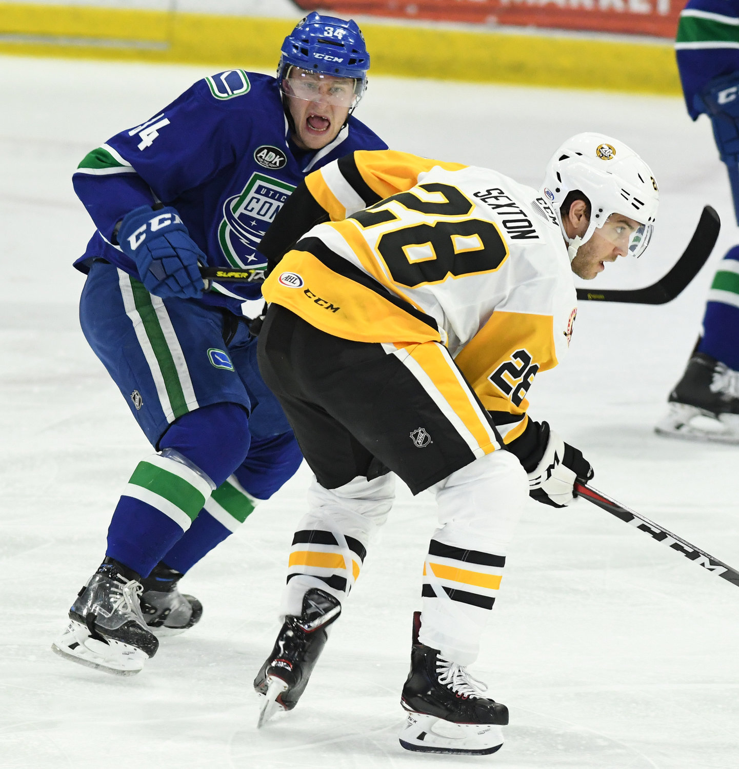 TOUGH GAME — Comets captain Carter Bancks, left, and Ben Sexton of Wilkes-Barre/Scranton  jockey for position in Friday night's game at the Utica Aud. The Comets won 8-1 in a game that included seven fights.