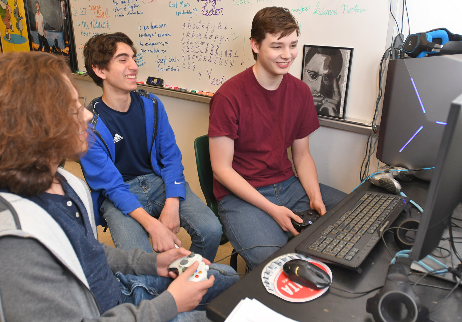 "AT THE CONTROLS — From left, Westmoreland High School students Nick Sovare, Patrick Amarasinghe and Brandon Massett play the ""Towerfall"" video game during a lunch period in global studies teacher Gianni Notaro's classroom. Notaro is adviser for the school's Esports Club."
