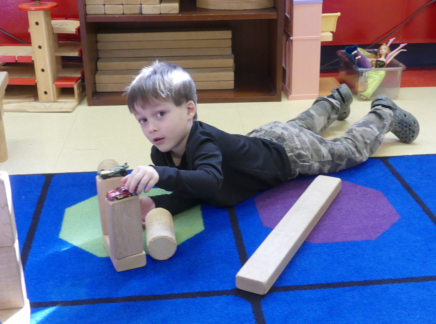 CONSTRUCTIVE PLAY — A child enrolled in the St. James Church Day School program in Clinton enjoys time building with blocks and playing with race cars during a special morning play time before academic activities.