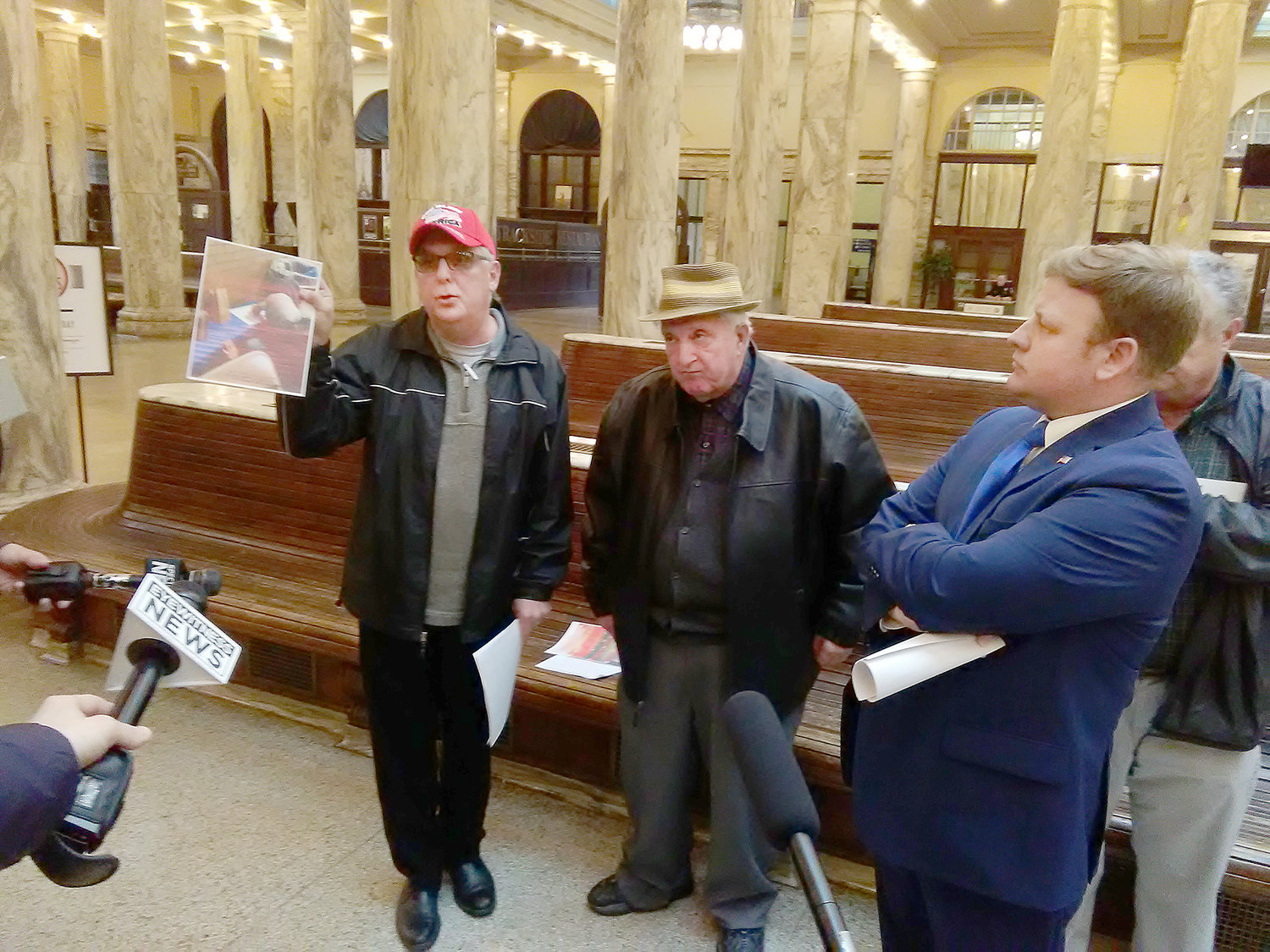 VOTING AT ISSUE — Jim Zecca of Utica shows a photo of voters filling out a provisional ballot at a poling place in November, while Lou Poccia, center, who was a poll watcher, and Oneida County executive Republican candidate David Gordon, right, look on at Union Station in Utica Monday.