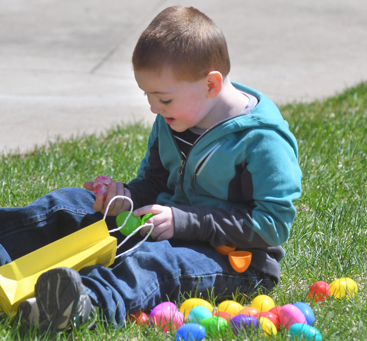 CRACKING THEM OPEN — Greyson Grant, 5, opens up Easter eggs he's gathered at the City Hall Easter Egg Hunt on the Girffo Green. He was at the event with his aunt Rachel Coleman and twin sister Hope Grant.