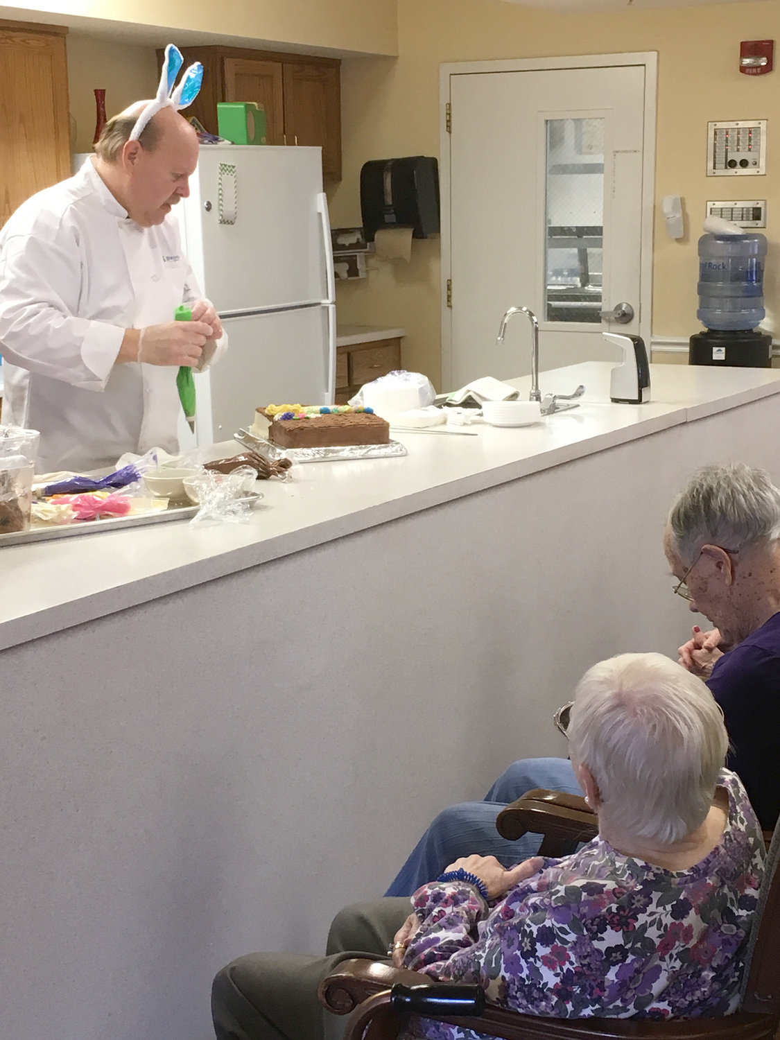 LEARNING EXPERIENCE — Residents of Brookdale Senior Living in Clinton watch as Chef Richard Fluharty demonstrates how to decorate an Easter basket carrot cake for the holidays.