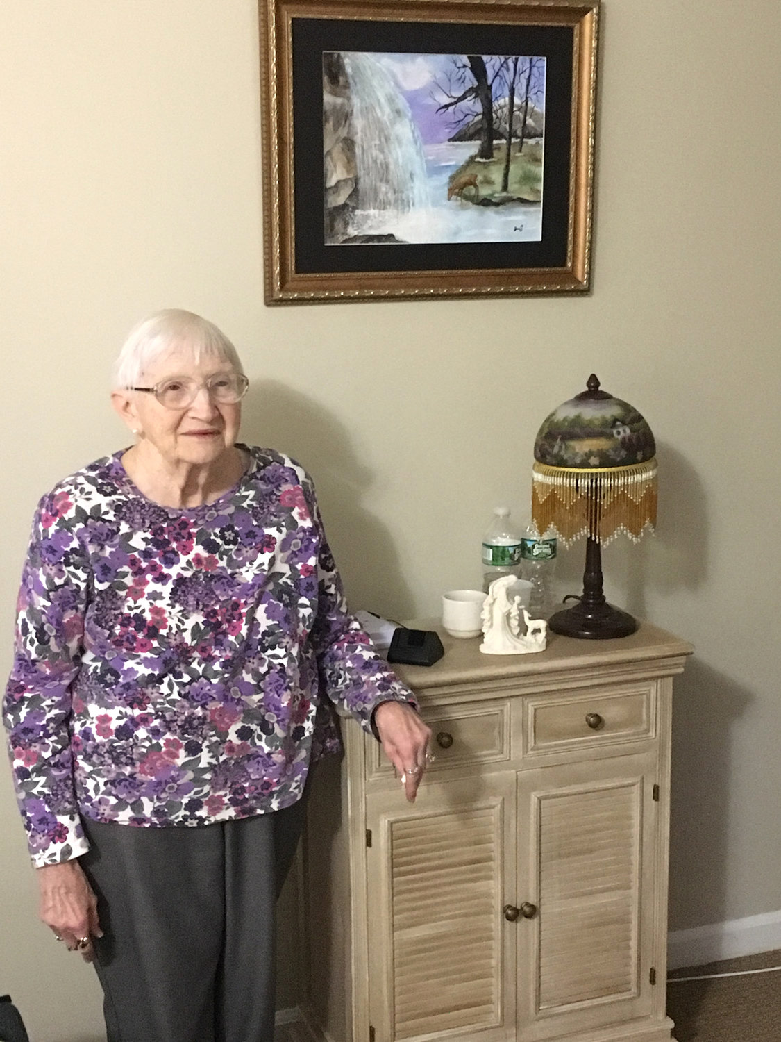 PERSONAL TOUCHES — Brookdale Senior Living resident Janice Schultz shows off one of the prized paintings she has created that hangs in her room.  Painting class is just one example of the several memory stimulating activities offered at Brookdale, and Schultz even helps to teach residents.