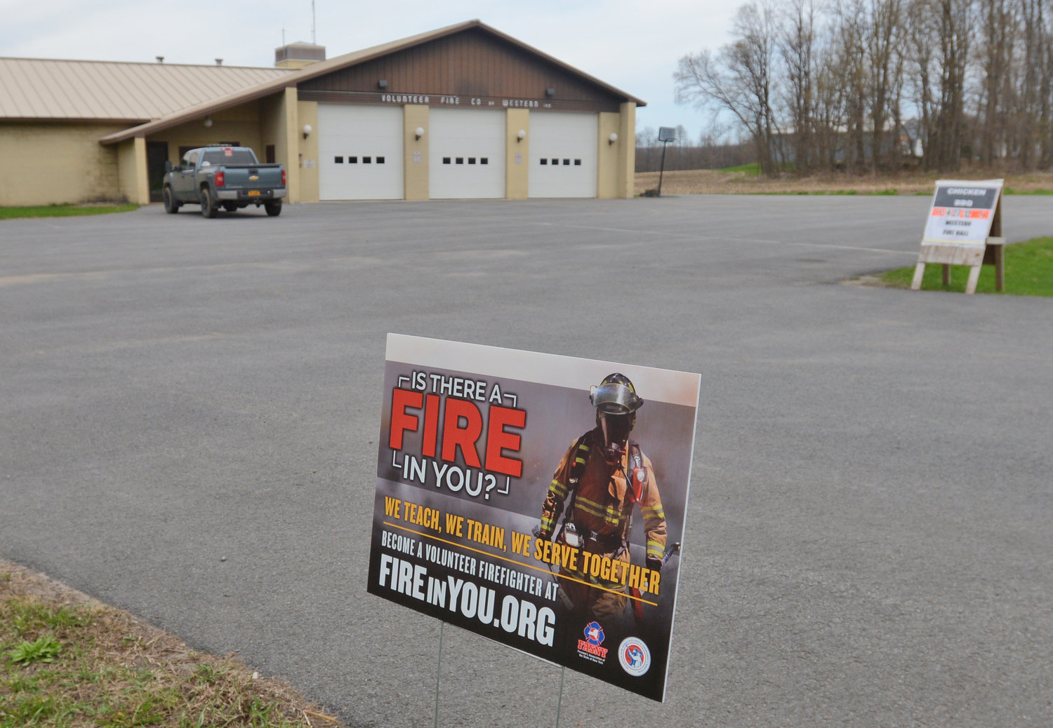 Western fire barn with a recruitment sign in the foreground.