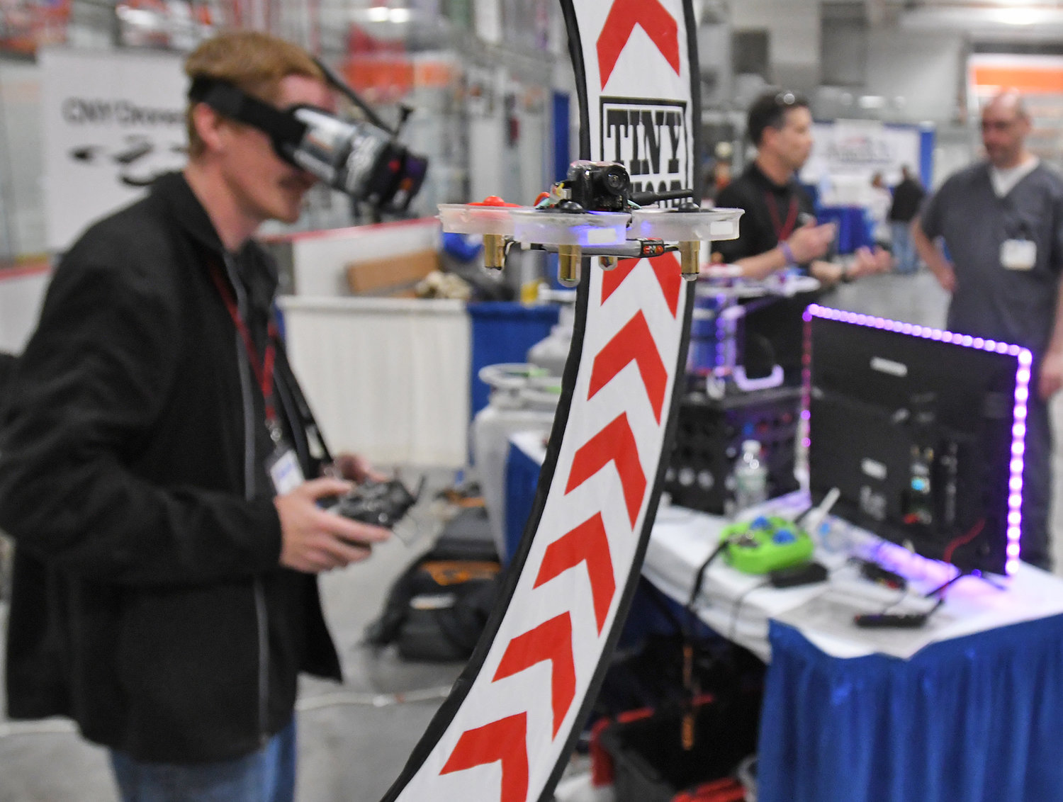 "TAKING FLIGHT — Aaron Diskin (background) of CNY Drones flies a small drone through loops at the Rome Home Expo Saturday afternoon. Rome Chamber President BIll Guglielmo said the drone exhibit was ""a big hit."""