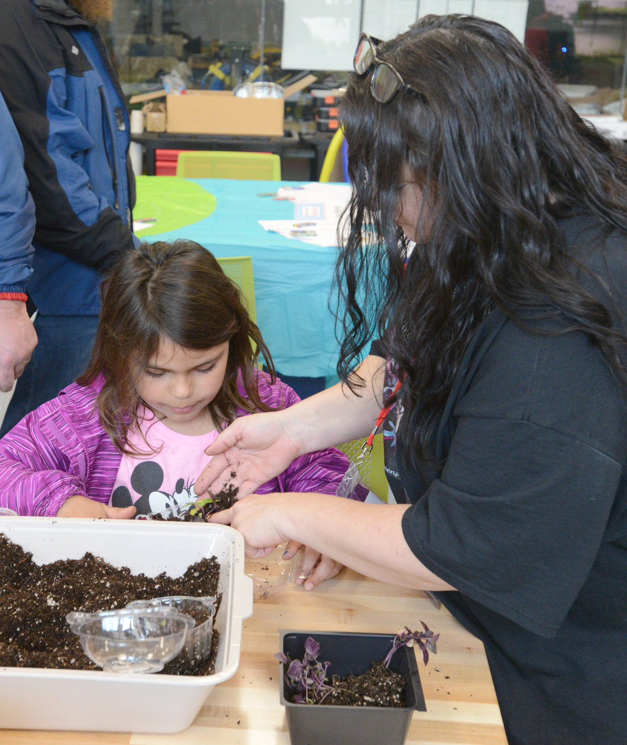 "GROWING GETS A HAND — Christina Carambia helps Kayle Frawley, 8, with planting purple varigated basil during the Mohawk Valley Mini Maker Faire on Saturday at SUNY Polytechnic Institute in Marcy. Frawley was at the event with her dad Ray Frawley, both from New Hartford. Carambia's start-up company, Underground Greens, ran a ""You Can Grow"" workshop to teach children how to garden. It was among various demonstrations and exhibits for the community at the event."