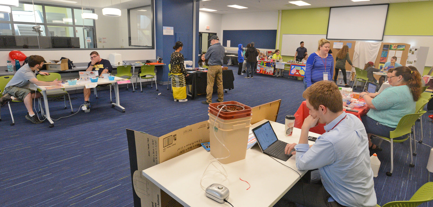 CHOICE OF ACTIVITIES — Above, Several exhibit tables with activities for the community were part of the Mohawk Valley Mini Maker Faire on April 20 at SUNY Polytechnic Institute in Marcy.