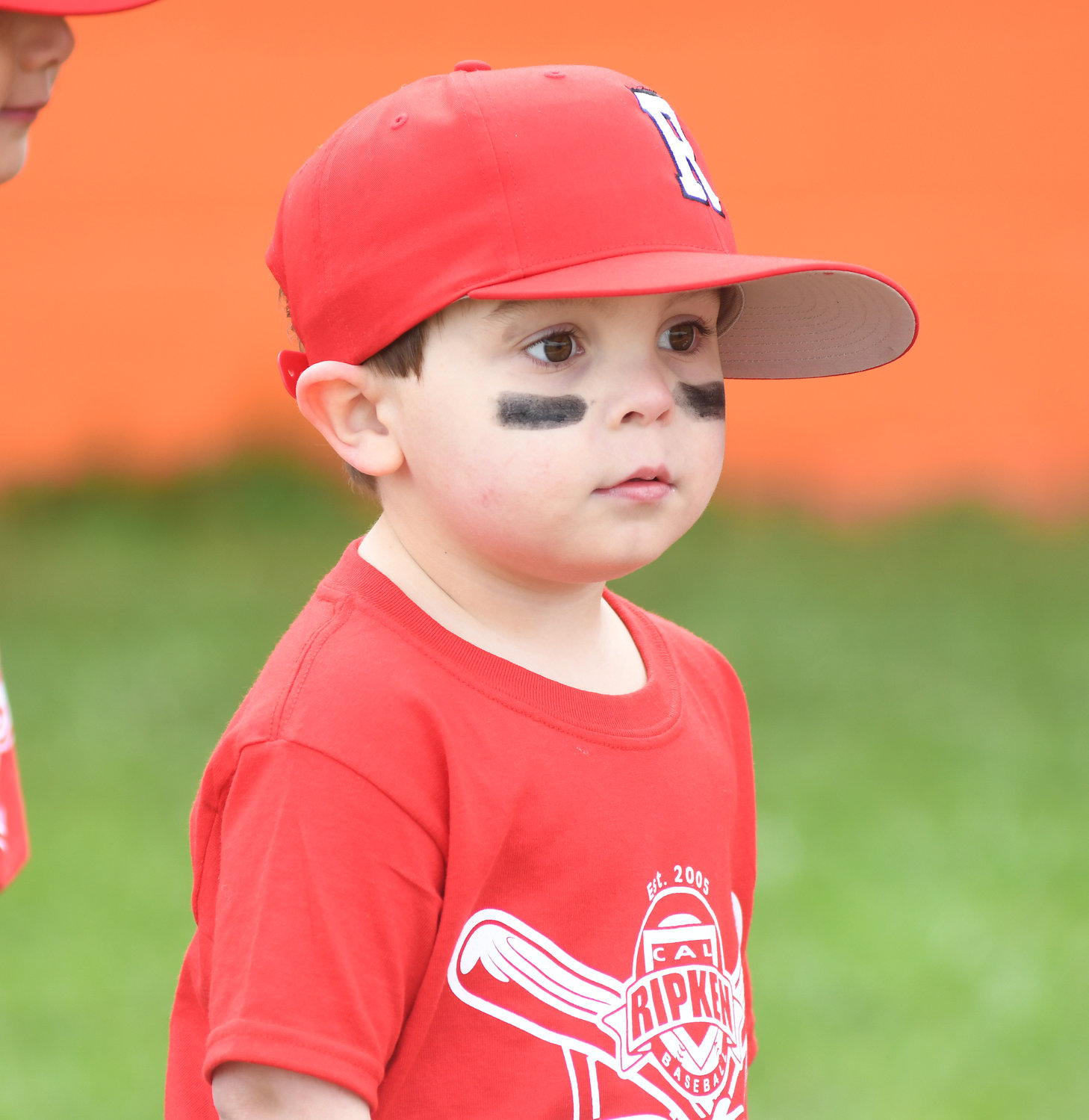 Ethan Wilkinson on the Rotary T-Ball team watches the ceremony that gets underway.