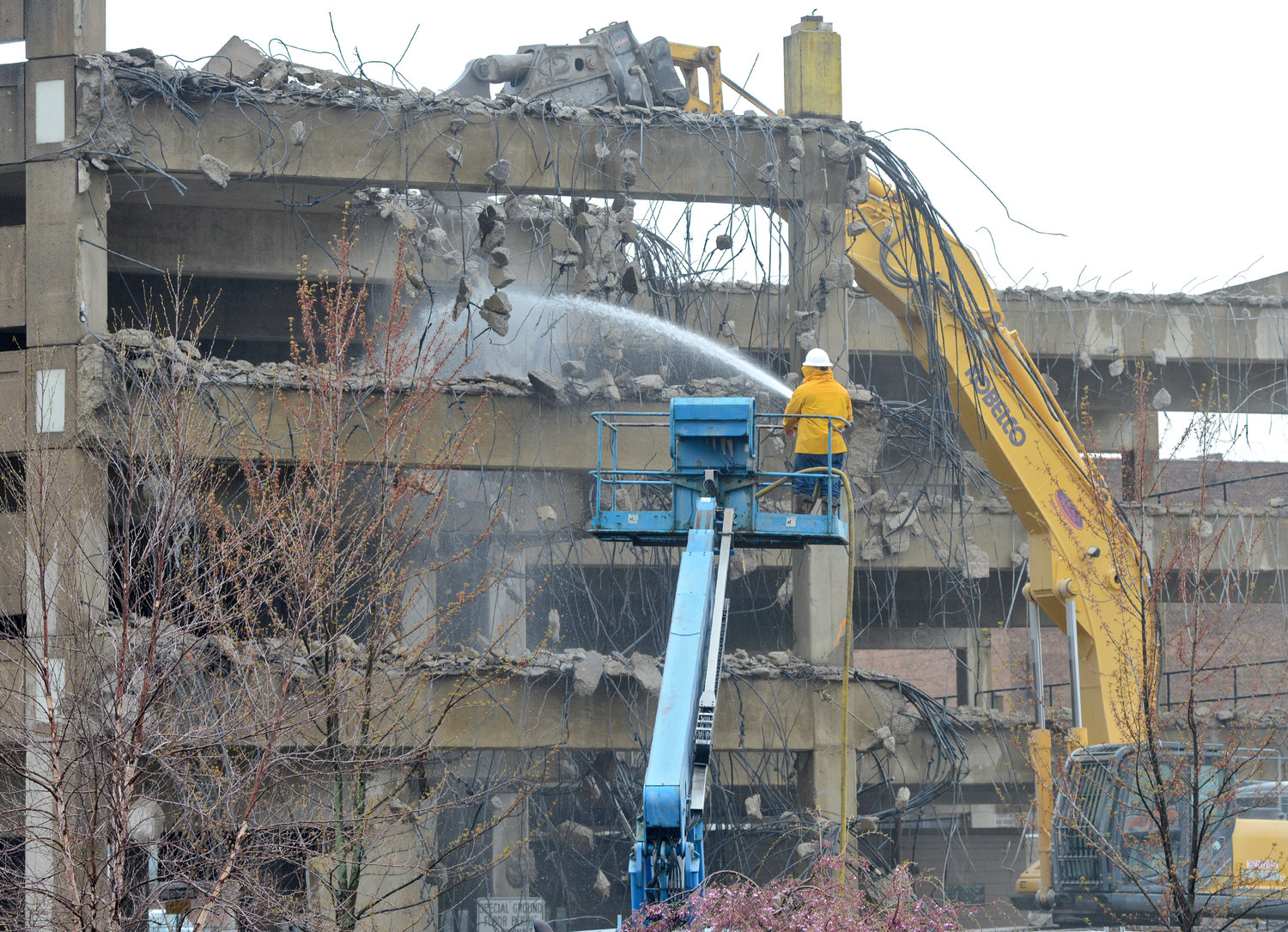 KEEPING THE DUST DOWN — A worker sprays water as a massive crane works to demolish the upper deck of the Liberty-North George Street parking garage on Friday morning. In her 2018 State of the City speech, Mayor Jacqueline M. Izzo pointed to the demolition project as a key element of the city's Downtown Revitalization  Initiative.
