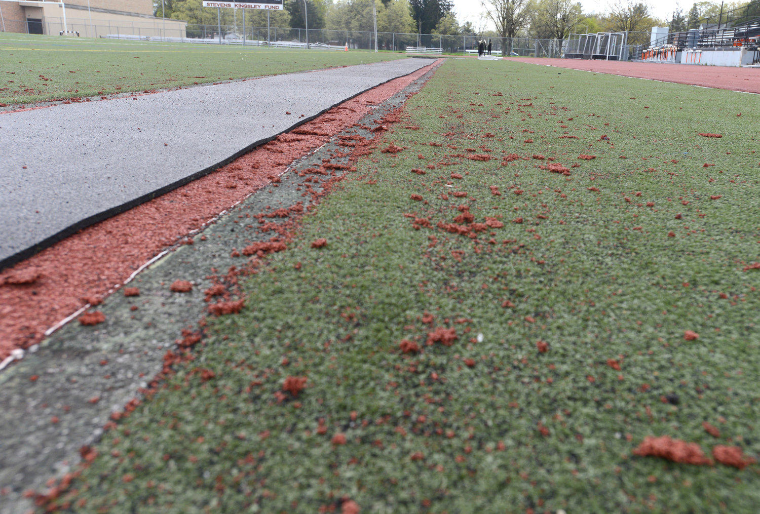 TORN UP — Pieces of the runway leading to the jumping pit on the west side of Rome Free Academy stadium are scattered about the facility's artificial turf.  The track, worn down by years of use and periodically patched and repaired, won't host any boys or girls varsity meets this year, according to school district officials, because of its condition.