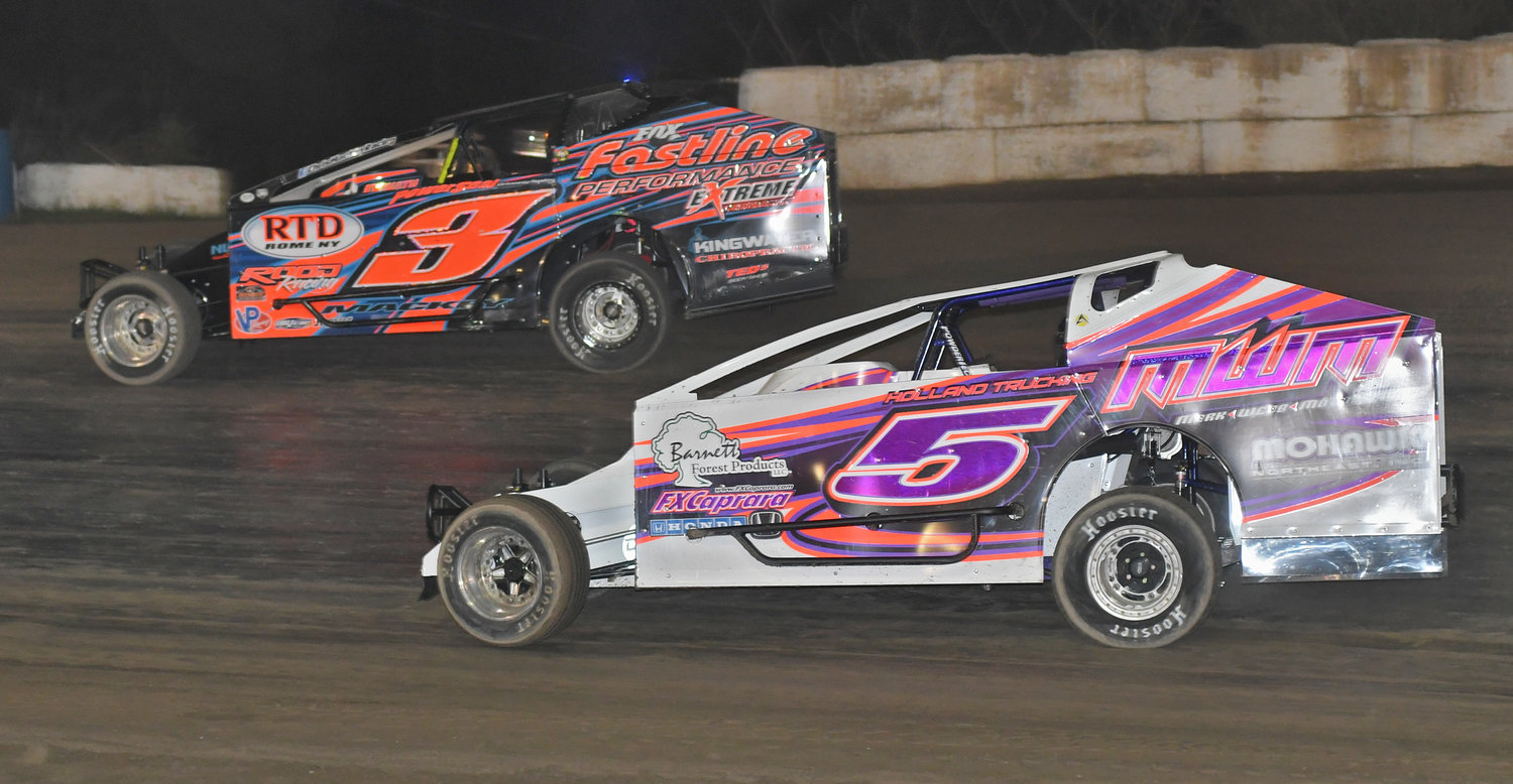 UP FRONT — Amy Holland, No. 5, works the low line where she was finding a lot of grip to put pressure on Rome's Chris Mackey, No. 3, during sportsman feature action last Saturday. Mackey ended up second and Holland was third.