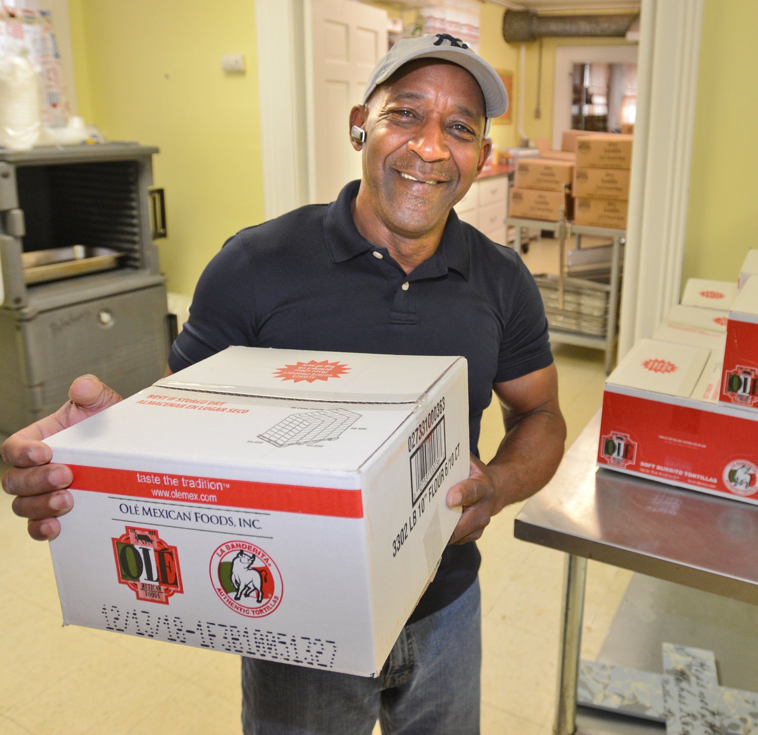 DOING GOD'S WORK — The Rev. Arthur F. Atkins Sr., pastor of Rome Wesleyan Church, moves boxes of perishables at the church's ministry, Bread of Life Community Center, located at 401 N. Washington St.  The center is in need of volunteers to help greet visitors, serve meals and deliver them, as well as monetary donations to expand its services to those in need.