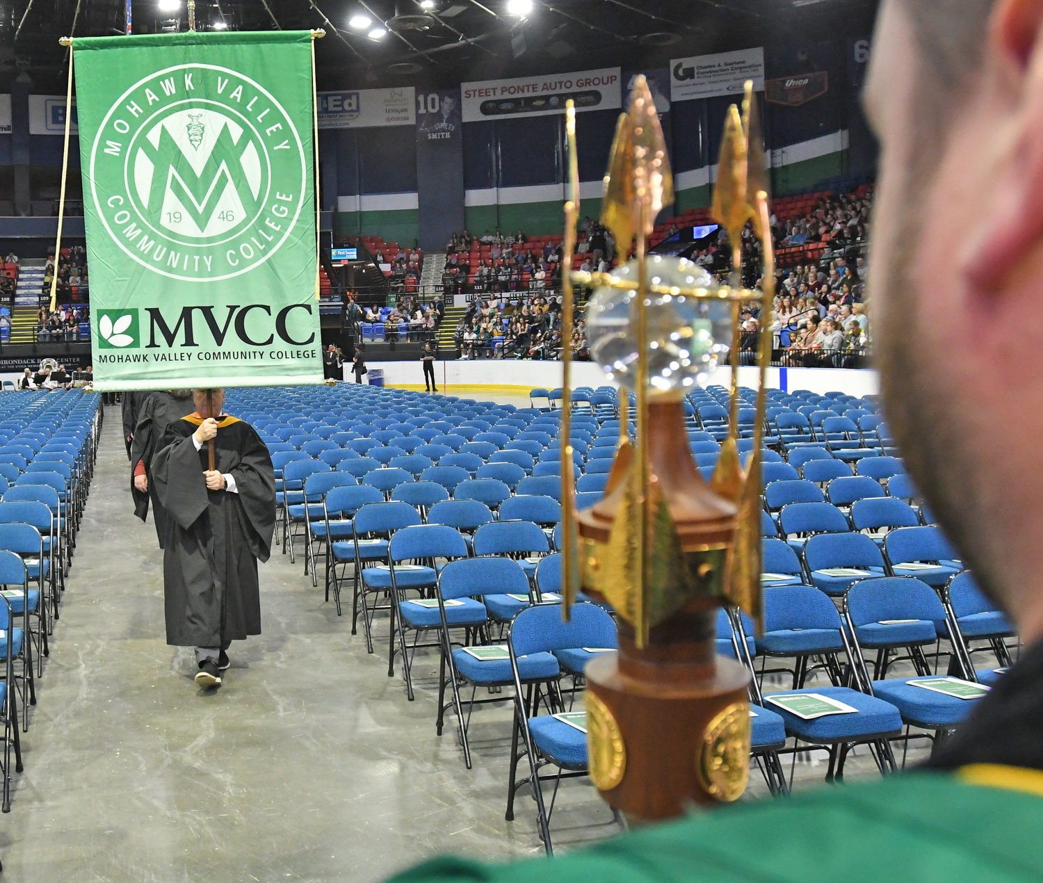 MAKING AN ENTRANCE — The Mohawk Valley Community College banner and mace lead the procession at the start of Mohawk Valley Community College's commencement ceremony on Thursday.