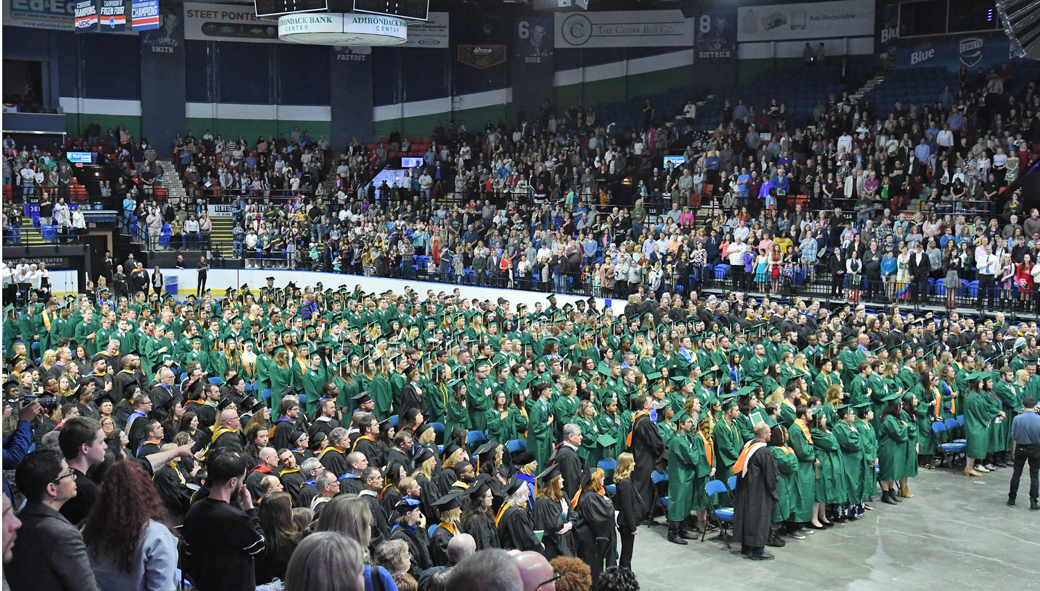 FILLED TO THE RAFTERS — A large crowd along with the candidates for graduation from Mohawk Valley Community College stand for the national anthem Thursday at the Adirondack Bank Center in Utica. More than 1,120 students at MVCC were eligible to walk the stage to receive their associates degrees or certificates, the college announced. This year's graduates join MVCC's more than 48,000 living alumni on record who have completed their studies at either, or both, of the college's campuses in Rome and Utica.