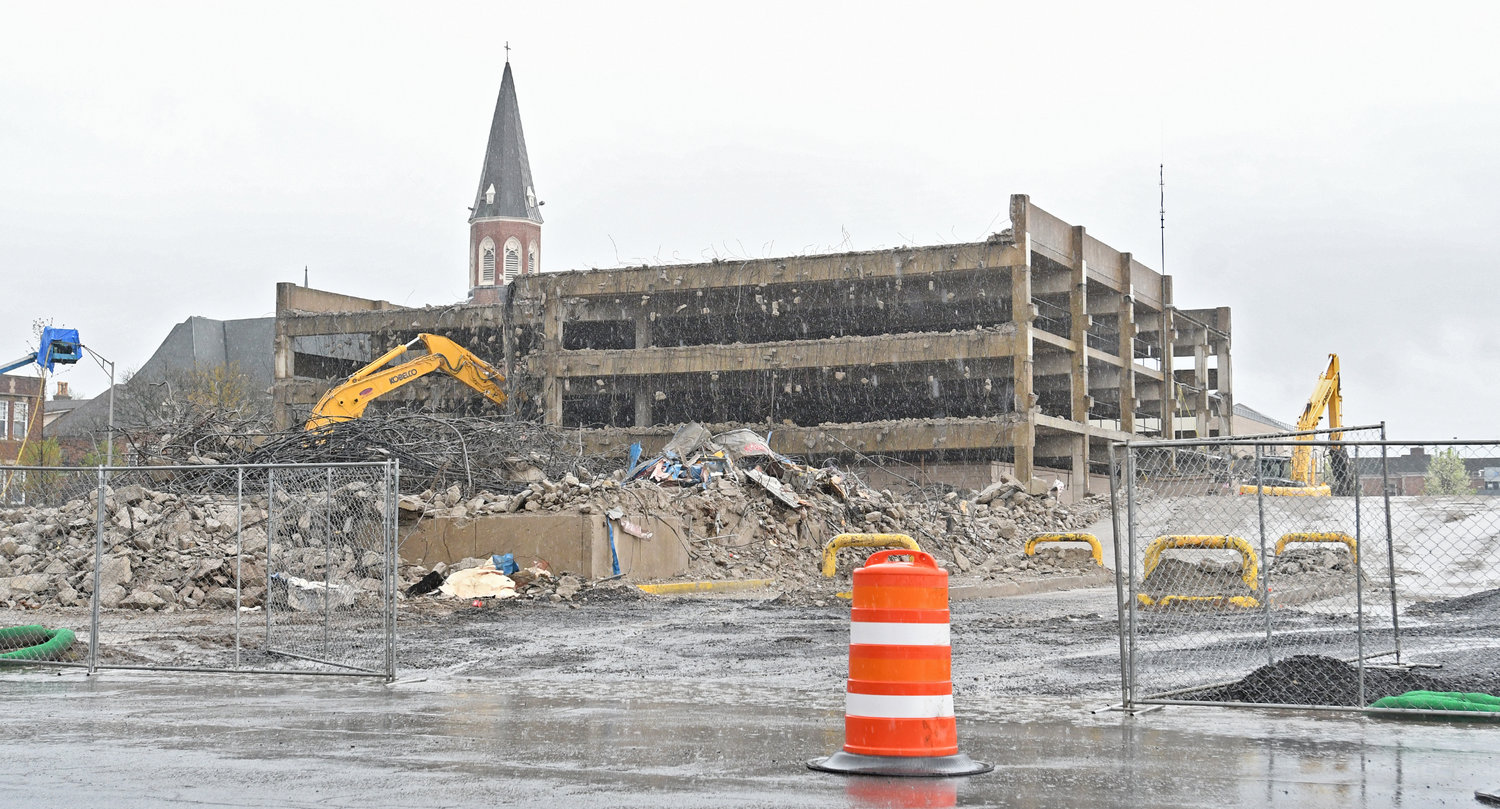 WET WORK — Demolition of the Liberty-George Parking Garage continues today despite a steady downpour. Asbestos found during the demo work will slow the rate of the project's completion and add to the cost, contractors told city officials.