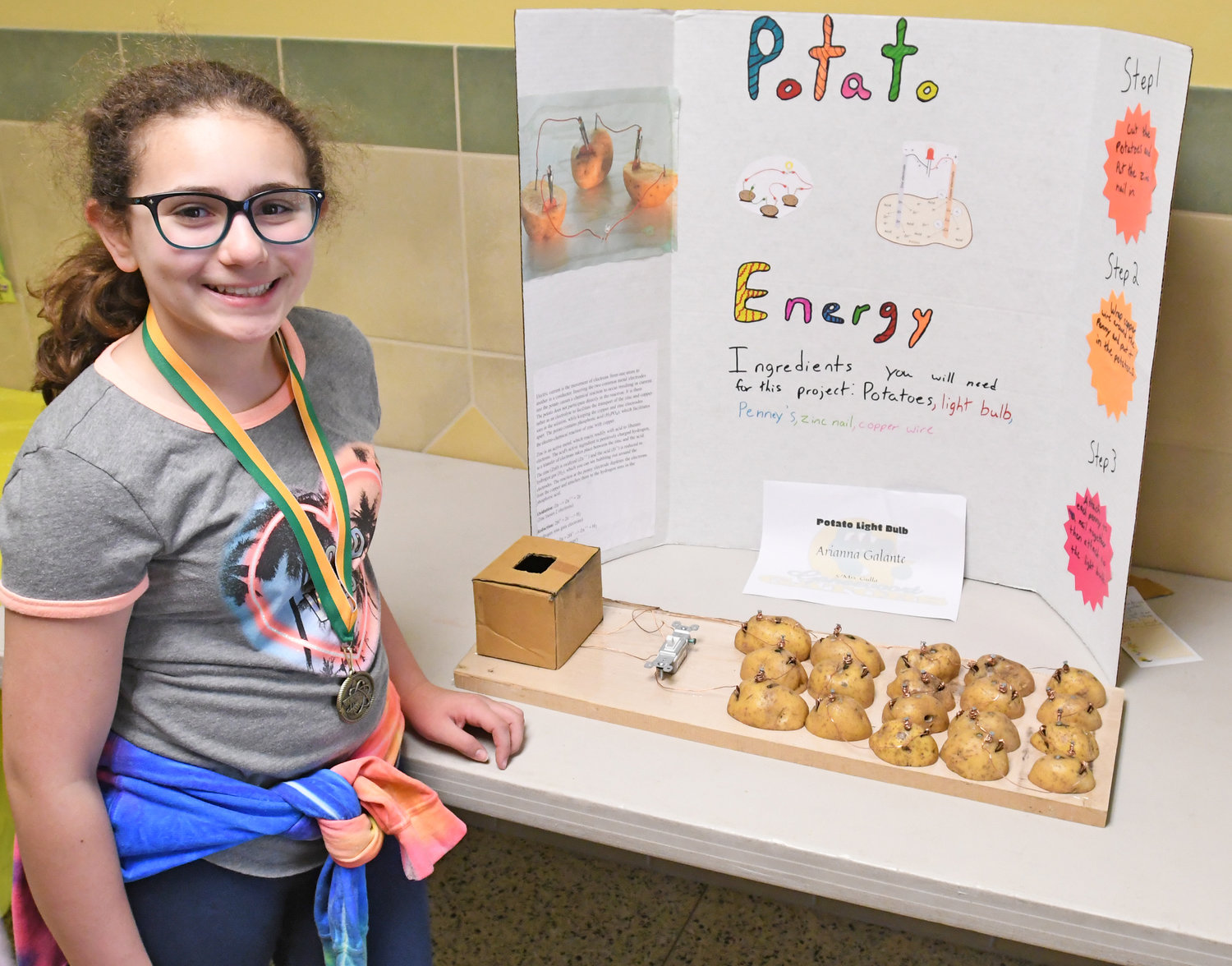 SPUD SPARKS — Arianna Galante, a fifth-grade student, poses with her Potato Energy display at the Gansevoort Elementary School Science Fair on Thursday.  Students at the West Liberty Street school conducted experiments and shared the results with fellow students, faculty, family and friends.