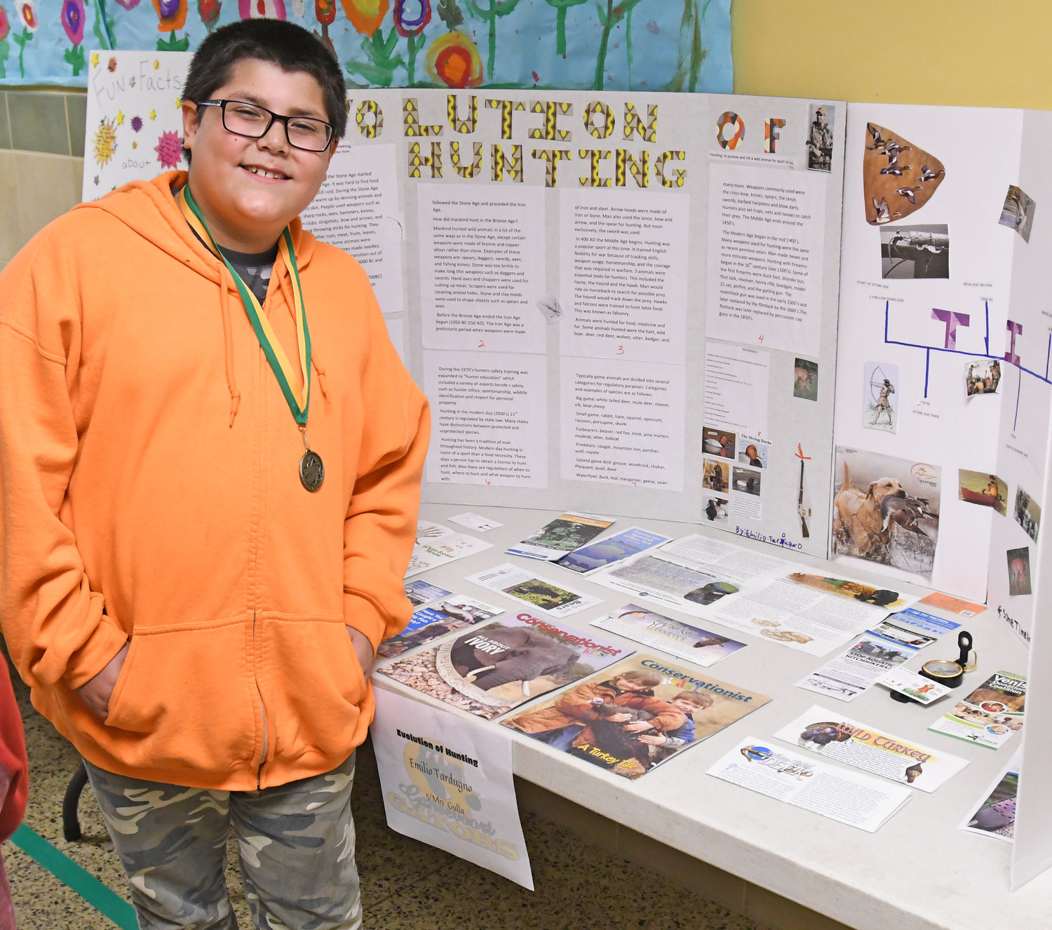 SHARING SCIENCE — Emilio Tardugno shows his display, complete with a variety of pamphlets, brochures and magazines, on the Evolution of Hunting at Gansevoort Elementary School's Science Fair on Thursday. Tardugno is a fifth-grade student.