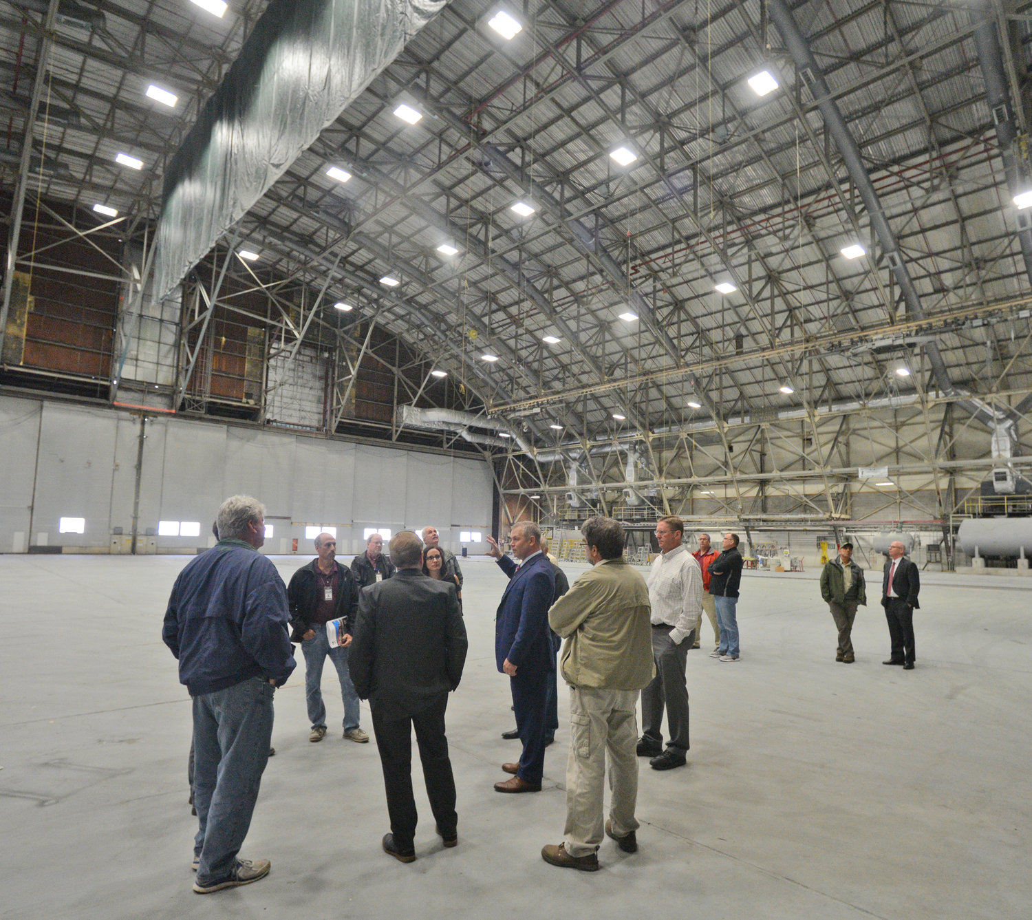 ROOM TO WORK — Aviation Commissioner Chad Lawrence talks with county legislators in the paint bay of building 101 at Griffiss International Airport. The former Air Force hangar was used to paint airplanes by a previous tenant company.