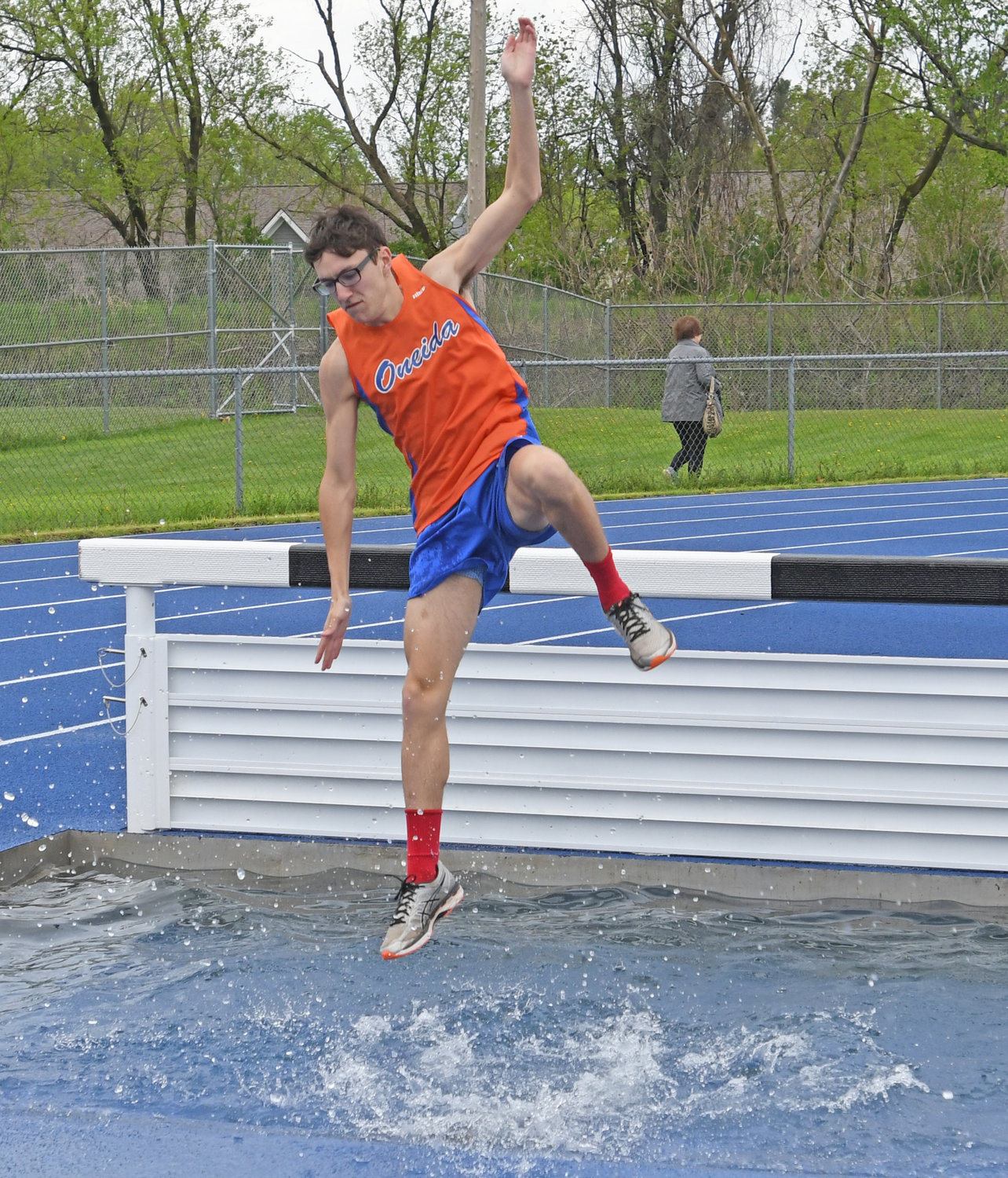 WATER LANDING — Philip White, a junior from Oneida, lands beyond the hurdle during the steeplechase Friday at the Oneida Invitational. He finished 15th in the event.