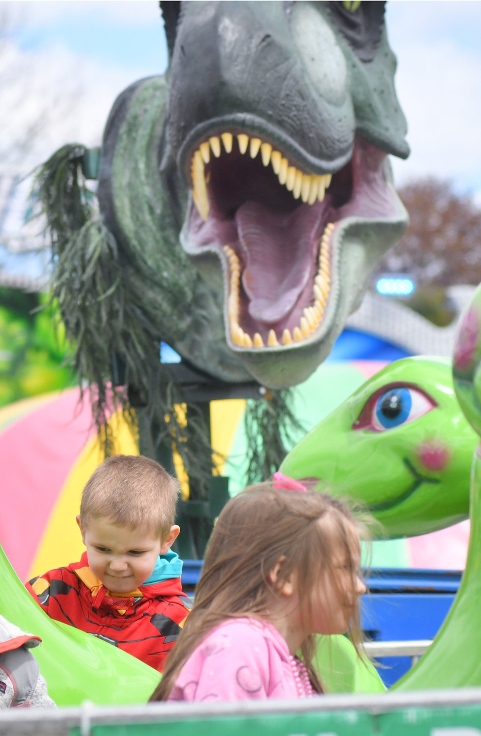 BEHIND YOU — A T-Rex is breathing down the neck of Parker Powers, 4, while his sister Kinley Powers, 5, is relatively safe in the foreground. The Powers and their parents, Sean and Kai, atteneded the Rome Catholic School Festival on Saturday afternooon.
