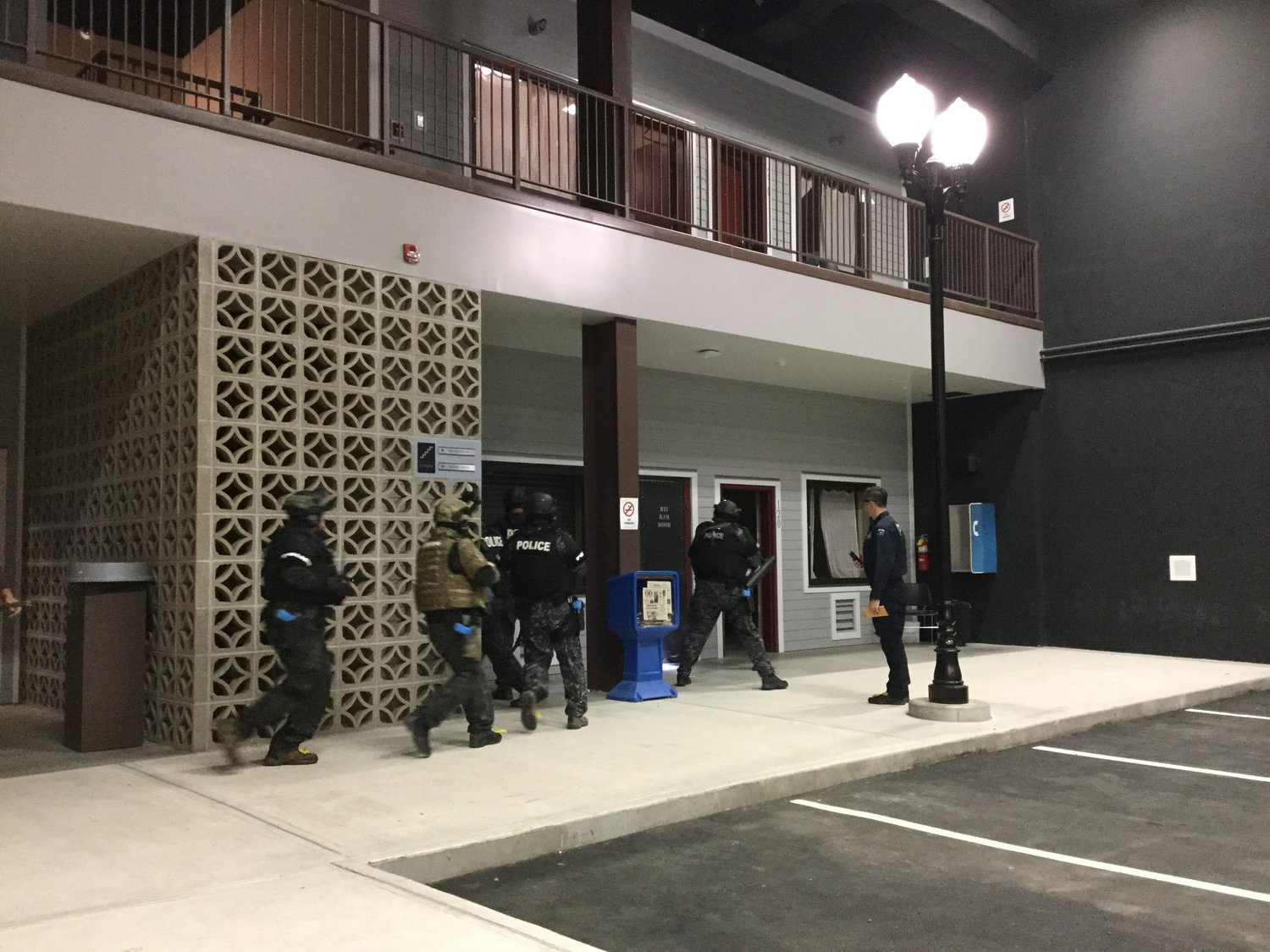RUSH THE DOOR — Members of the Utica Metro SWAT team storm the fake motel facade at the state Preparedness Training Center in Whitestown. The physical challenge involved busting down three barricaded doors, including one on the second floor of the motel.