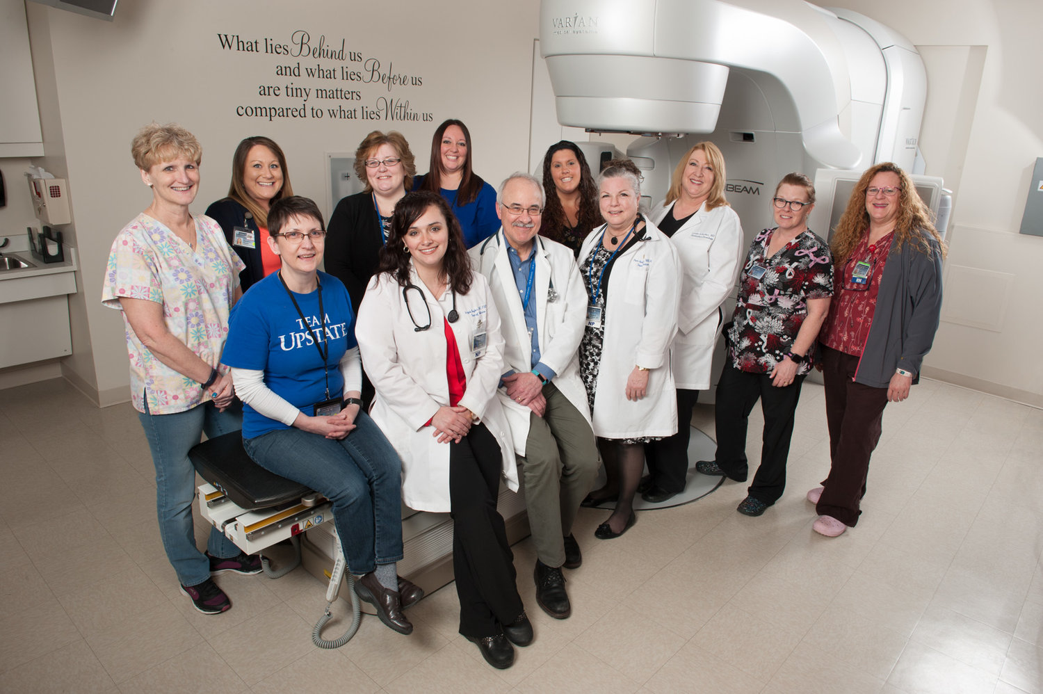 CELEBRATING — Staff of the Upstate Cancer Center at Oneida include, back row from left: Cindy Norman, Rachel Relyea, Kelly Moore, Lindsey Phillips and Jamie Palumbo. Front row, from left: Linda Mantz, Angela Taylor, Steven Graziano, Pam Salisbury, Linda Schicker, Julie Matthews and Amy Jennings.