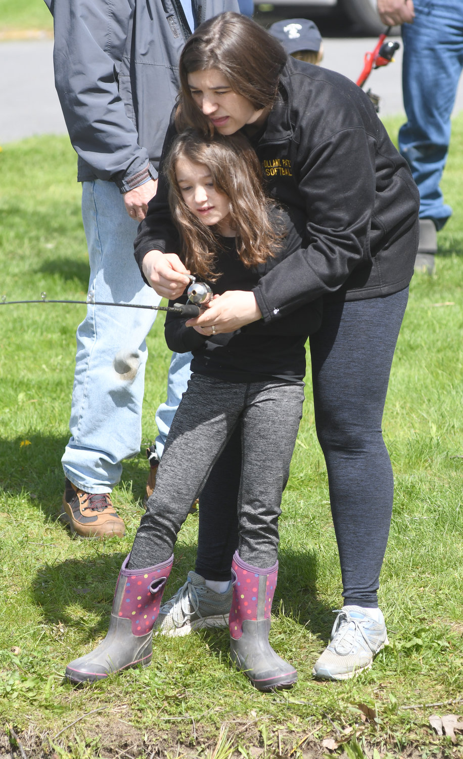 TEAM EFFORT — Heather Roberts and her daughter Ellie reel in a whooper of a fish during the Rick LeFevre Fishing Derby. Rick LeFevre, a longtime city Recreation Department worker, was Heather's uncle.