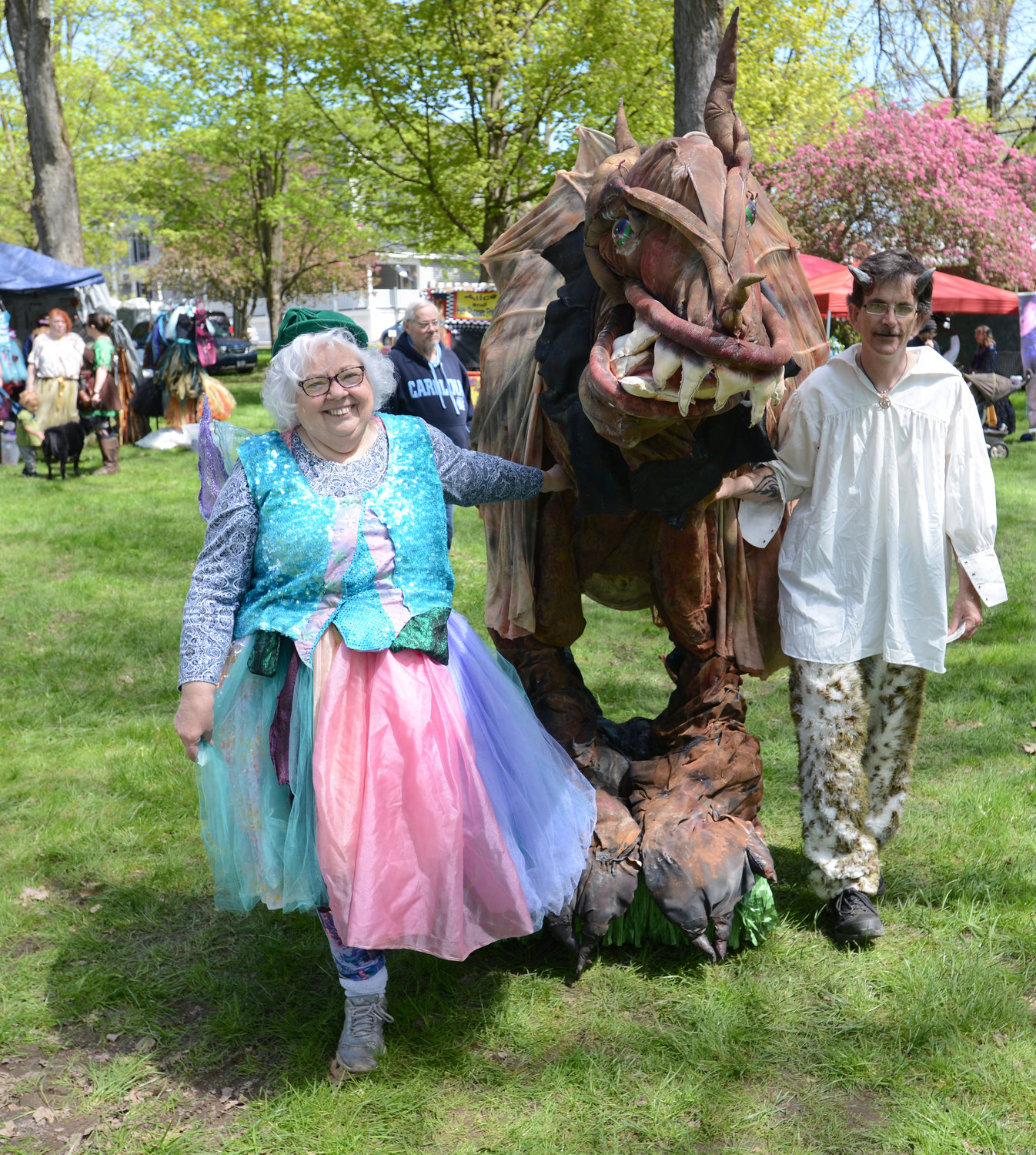 DRAGON WALK — Puppeteer Alice Dennis walks her dragon ARFF with David VanValkenburgh at the Holland Patent Mayfaire on the Green on Saturday.