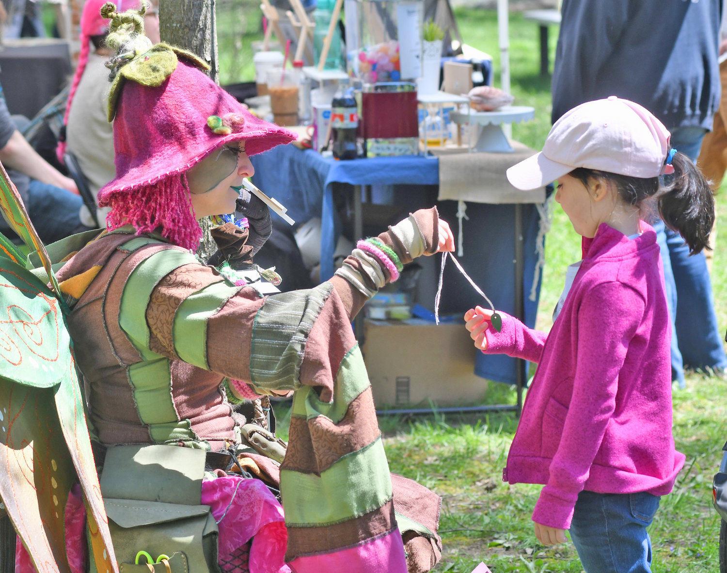 WINNINGS — After playing a game, Thimbleberry the Woodsprite gives a prize to Alana Pratt, 6, daughter of Jeff Sullivan and Shamariah Pratt-Sullivan of New Hartford at the Mayfaire on the Green in Holland Patent on Saturday.