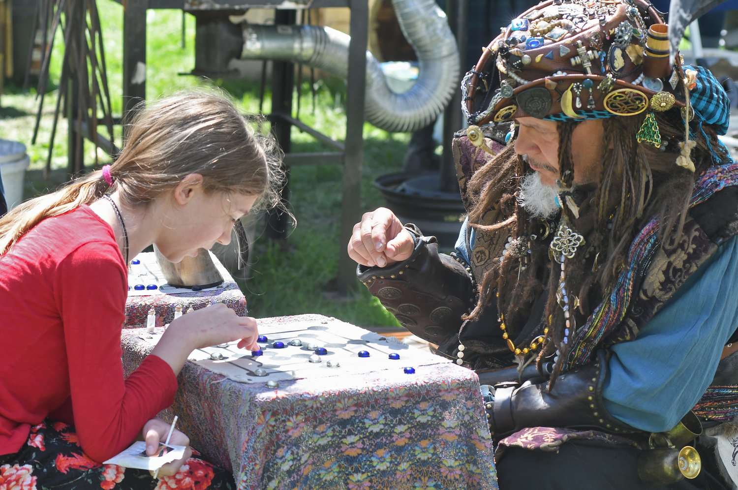 RENAISSANCE RECREATION — Katreena Natschke of Taberg tries the ancient board game of Nine Men's Morris against Capt. Armand Barrera of Amsterdam at the Holland Patent Mayfaire on the green Saturday.