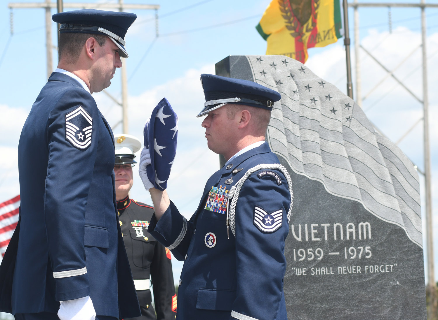 SMSgt Thomas L. Whiteman is presented the folded American flag from TSgt Lee R. Settle during the Vietnam Memorial dedication ceremony.