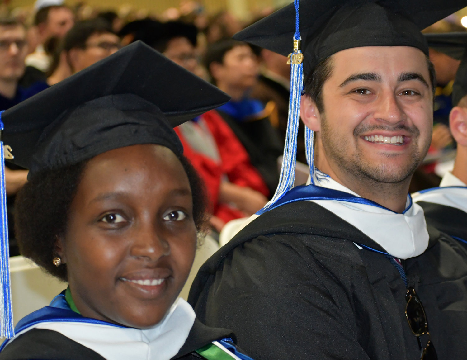 PROUD DAY — Hamilton College Class of 2019 graduates Risper Kirvi of Kenya, East Africa and Jonathan Kirshenbaum of Newton, Mass. were all smiles as they prepared to receive their degrees at the Hamilton College commencement ceremony on Sunday, May 26 in the Margaret Bundy Scott Field House.