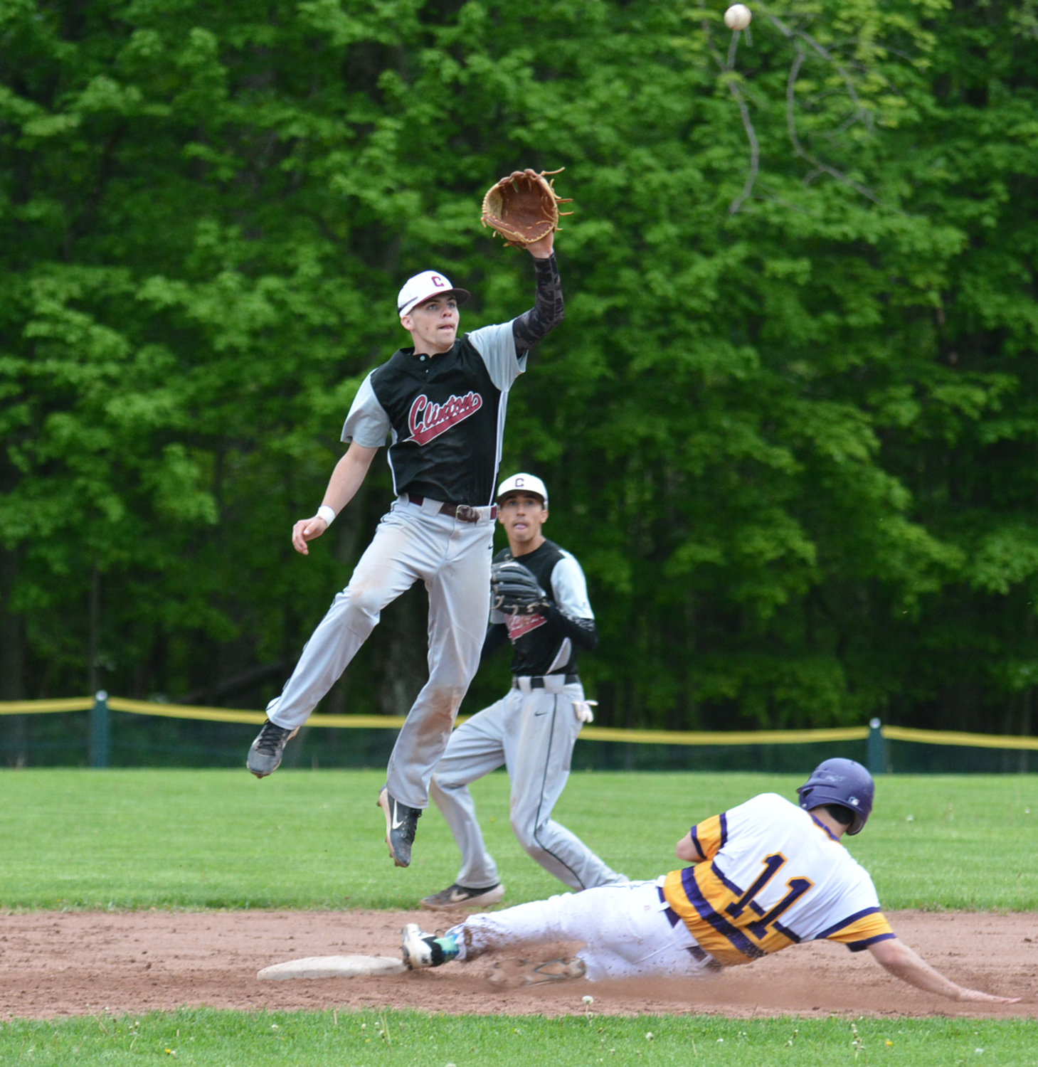 GOING UP GRAB — Clinton shortstop Tanner Deveans goes up for the high throw and misses the tag on Holland Patent's Mike Benedetto Friday, May 24 at Holland Patent High School.  It was the third meeting of these two teams this season and Holland Patent holds the top spot in the conference. The Golden Knights were 2-0 over the Warriors this season, but Clinton had their night and came away with a 5-3 win in Center State Conference play to go up 5-4 in the division and 8-8 overall.