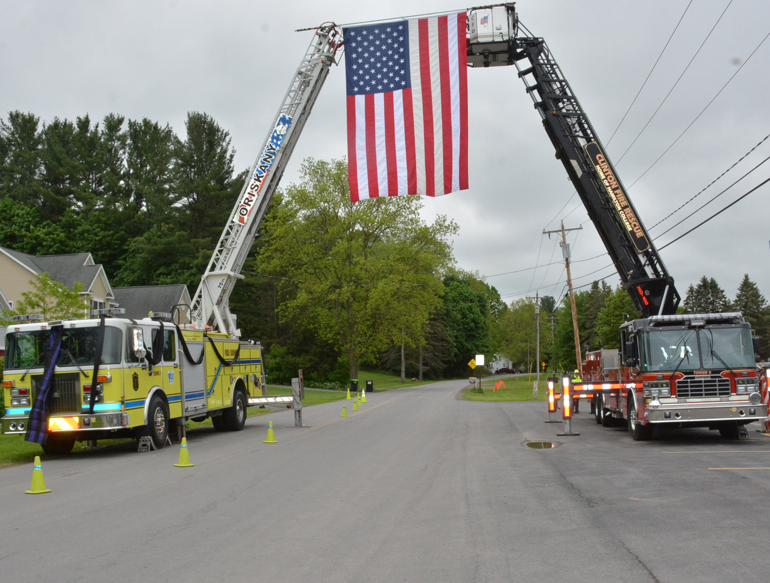 LADDER TRUCK TRIBUTE — The Clinton Fire Department and Oriskany Fire Department came together to honor deceased Willowvale Fire Co. Fire Chief Wayne Smoulcey on Franklin Avenue in Clinton on Wednesday, May 29. A funeral procession carrying the honored dead travelled underneath the tribute en route to the Sunset Hill Cemetery.