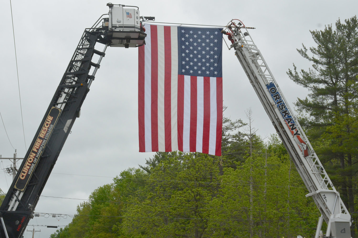 DEPARTMENTS BAND TOGETHER — The Clinton and Oriskany Volunteer Fire Departments hoisted the flag in honor of Willowvale Fire Co. Fire Chief Wayne Smoulcey on Franklin Ave. in Clinton on Wednesday, May 29. The funeral procession involved Utica and Kirkland Police Departments, also the Oneida County Sheriffs Office as it carried the honored dead to his final resting place at the Sunset Hill Cemetery.