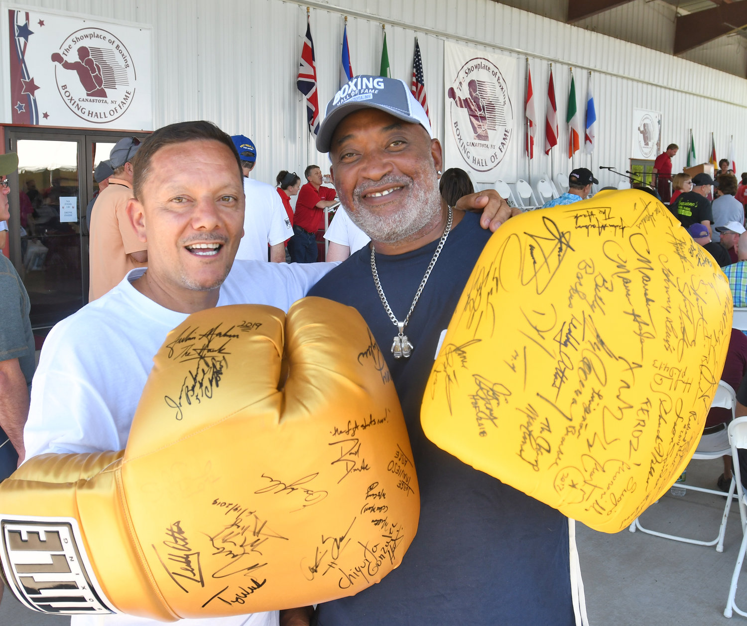 ALL SMILES — Antonio Ocasio and Albert Suarez from the Bronx hold up their big boxing gloves at the International Boxing Hall of Fame in Canastota on Friday afternoon. The men were looking forward to adding to their autograph collection during Boxing Hall of Fame weekend.