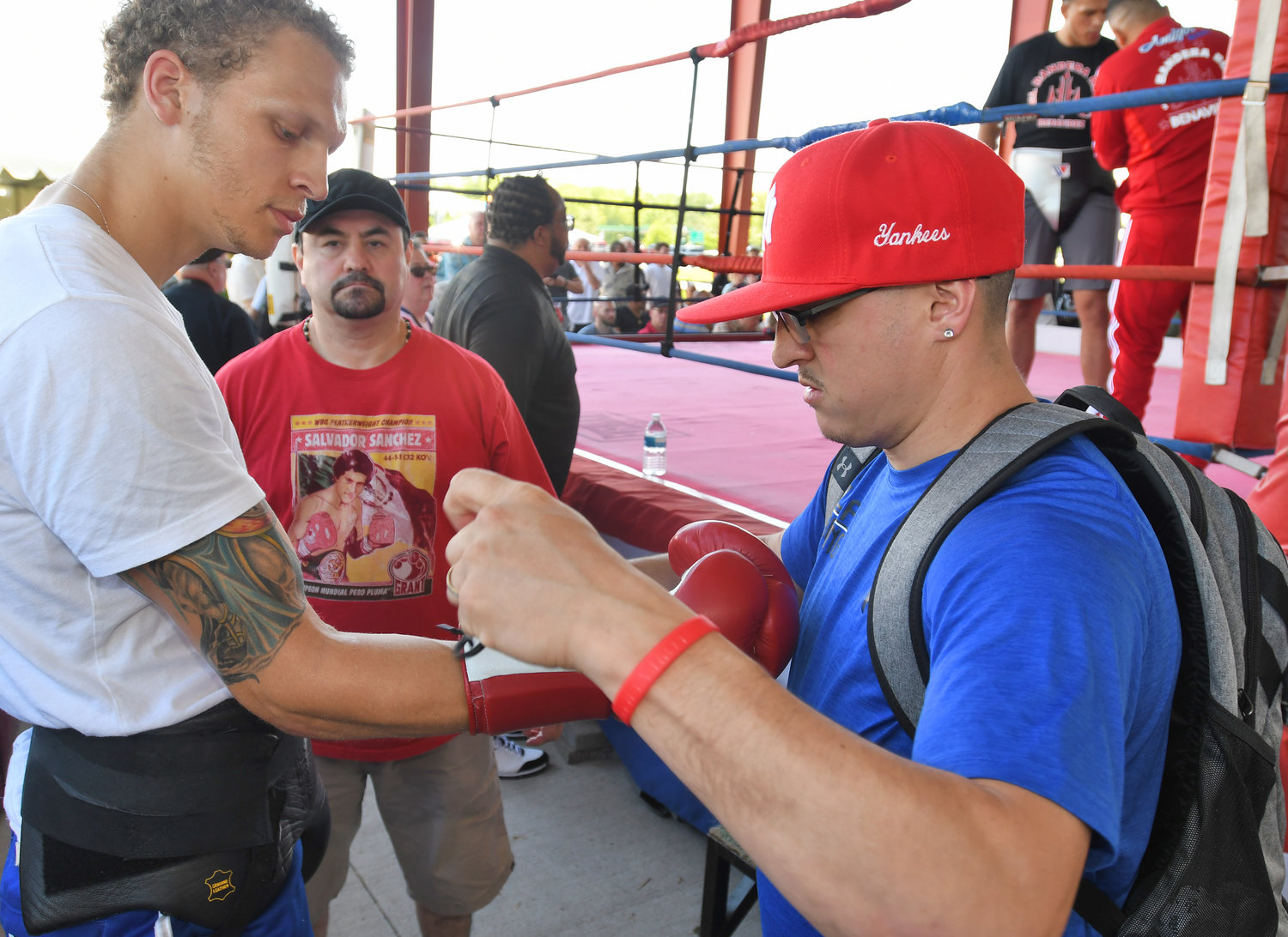 "LACING UP THE GLOVES — Utica boxer Micheal Rycraft has his boxing glove laced up by Timothy Nolan from the Rochester Fight Factory on Friday afternoon at the International Boxing Hall of Fame in Canastota. Rycraft was on hand to spar with former World Boxing Council super middleweight champion and top-ranked contender David ""El Bandera Roja"" Benavidez."