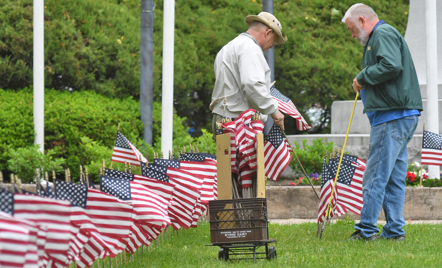 IT'S A GRAND OLD FLAG...ALL 3,500 OF THEM — Duane Niemi, left, and Ron Witt place some of the 3,500 flags that will adorn the twin parks — Veterans Memorial Park and Gansevoort Park — on the 200-block of North James Street for Flag Day on Thursday. Longtime Rome Veterans Committee member Tom Kenealy said that over the past seven years, the group, led by a dedicated core group of volunteers, has put out about 20,000 flags to honor America. Additional photo, page 2.