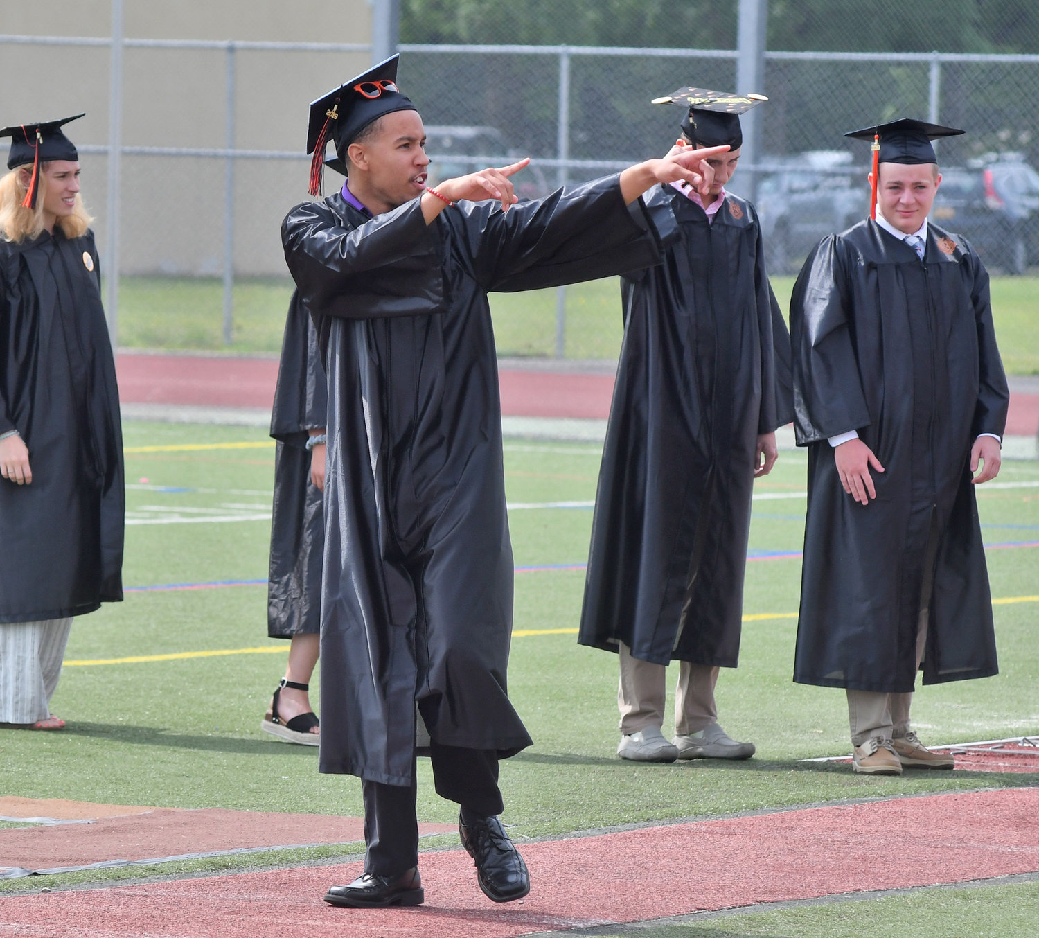 HERE'S TO YOU — Jerome B. Gordon points to the crowd as he walks to receive his diploma during the Rome Free Academy commencement Saturday.