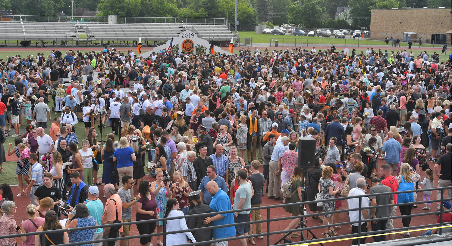 ENJOYING THE CROWD — Happy graduates gather with family and friends on the turf at Rome Free Academy Stadium following the conclusion of RFA's 150th commencement Saturday.