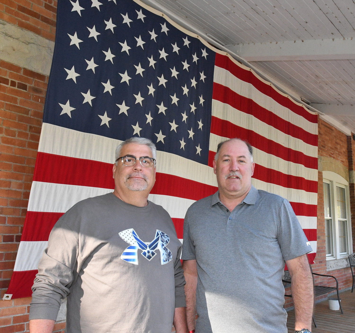 PARTY ON THE PORCH — Clark Mills American Legion Post 26 Commander Jim Nolan, left, and Past Commander Butch Bellows, stand in front of Old Glory on the front porch of Post 26 during the chapter's Party on the Porch event on June 14.