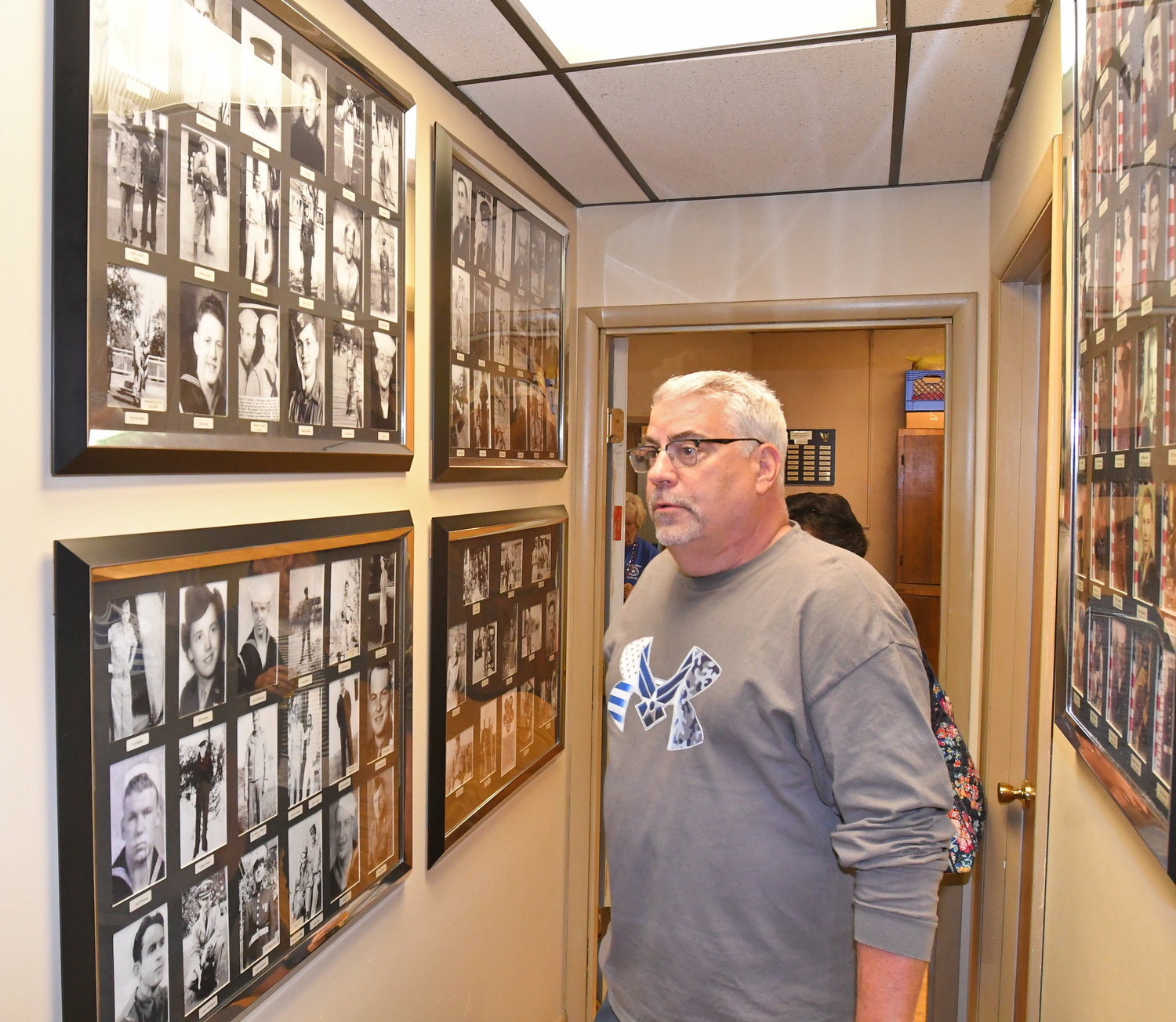PIECES OF THE PAST — Clark Mills American Legion Commander Jim Nolan looks over photos recently added to the walls of Post 26 during the chapter's Party on the Porch event on June 14.